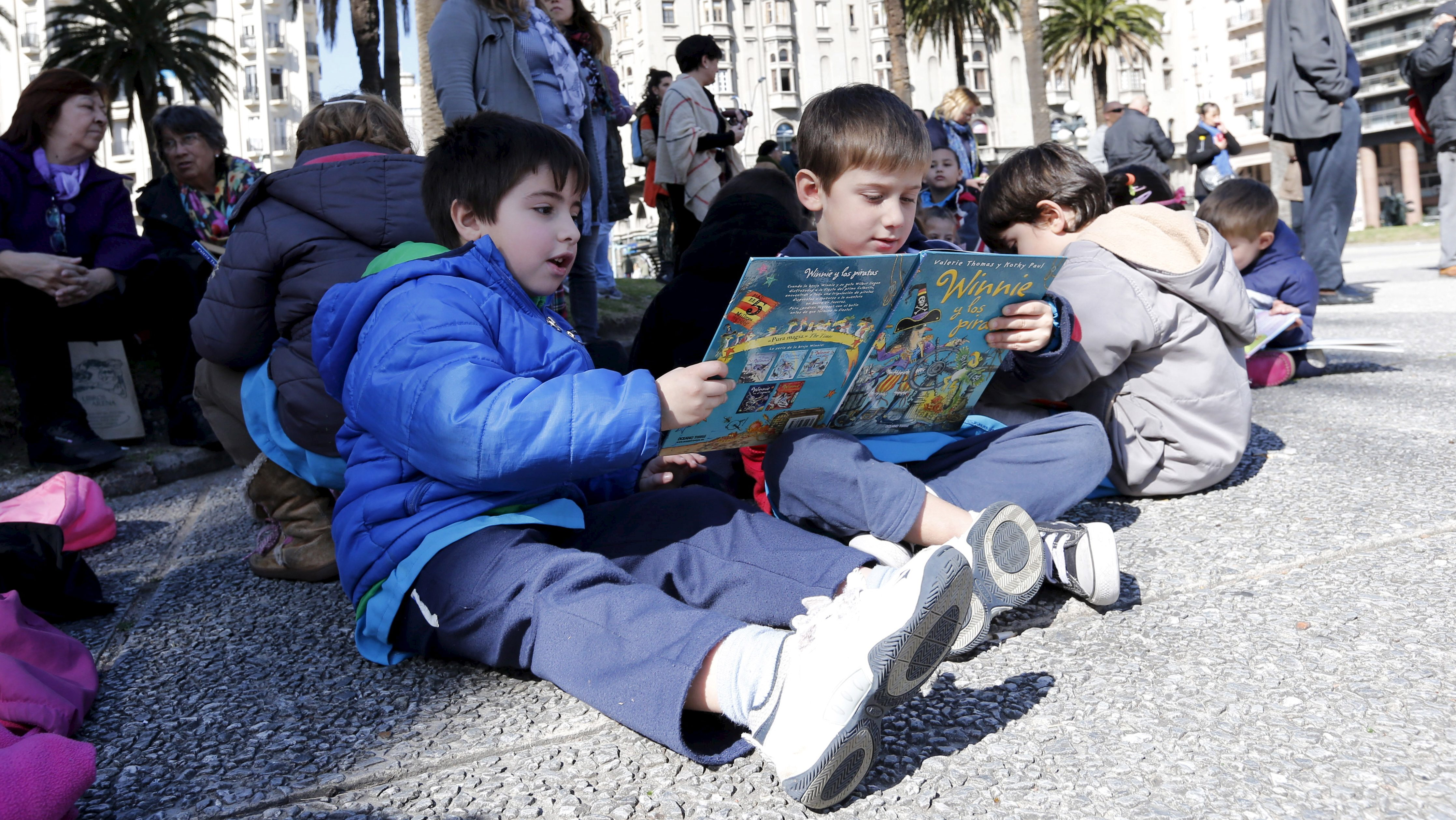 "Children read books at Montevideo's Independencia square while participating  in the activity ""Al Aire Libro"" that encourages reading in public spaces, September 4, 2015.  REUTERS/Andres Stapff  - RTX1R5PM"