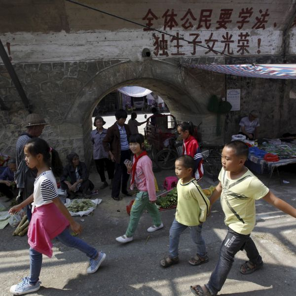 Children walk past a one-child policy slogan written on a wall at a market in Futang village of Liuzhou