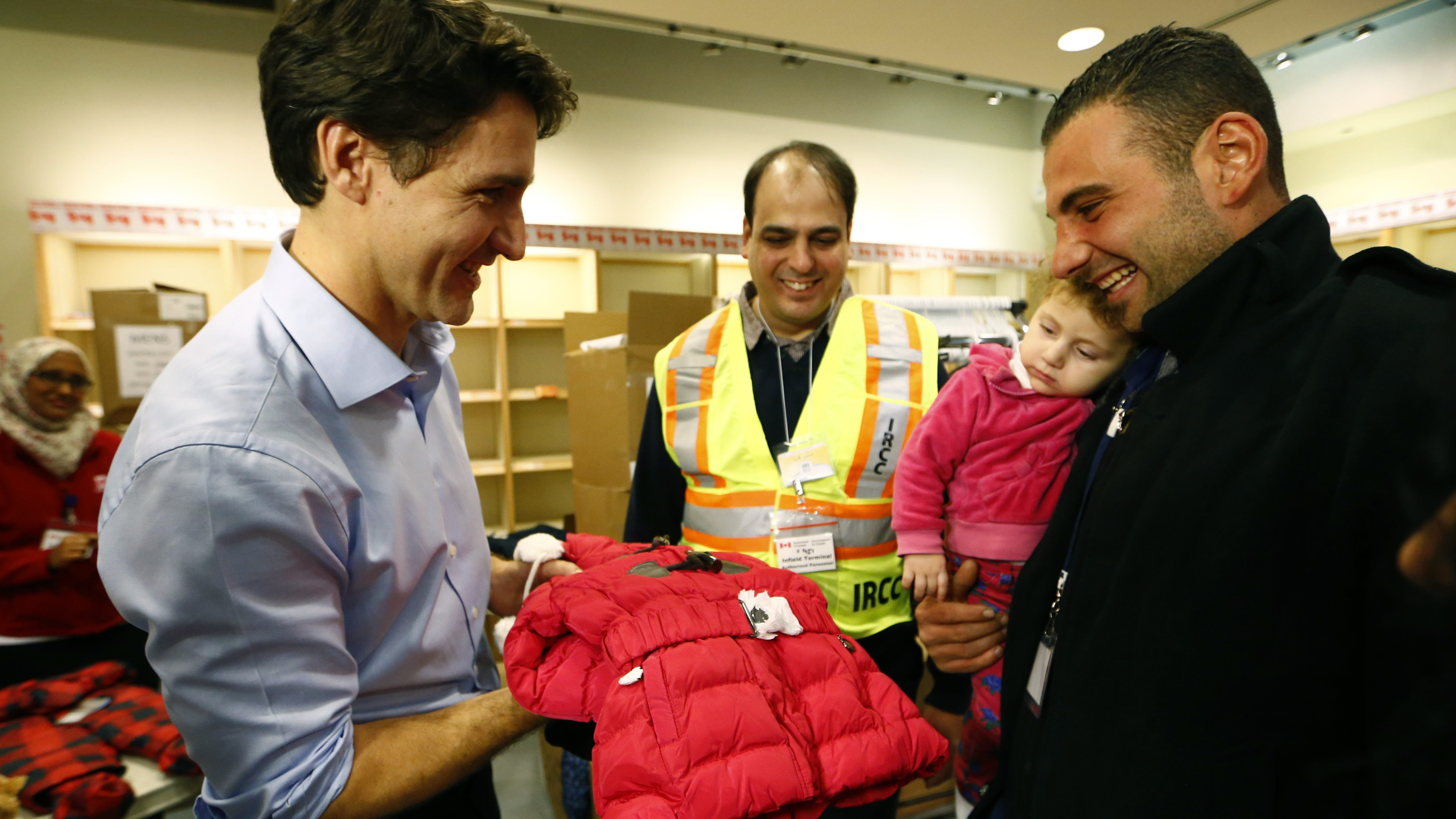 Syrian refugees are presented with a child's winter jacket by Canada's Prime Minister Justin Trudeau (L) on their arrival from Beirut at the Toronto Pearson International Airport in Mississauga, Ontario, Canada December 11, 2015. After months of promises and weeks of preparation, the first Canadian government planeload of Syrian refugees landed in Toronto on Thursday, aboard a military aircraft met by Prime Minister Justin Trudeau.