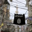 An Islamic State flag hangs amid electric wires over a street