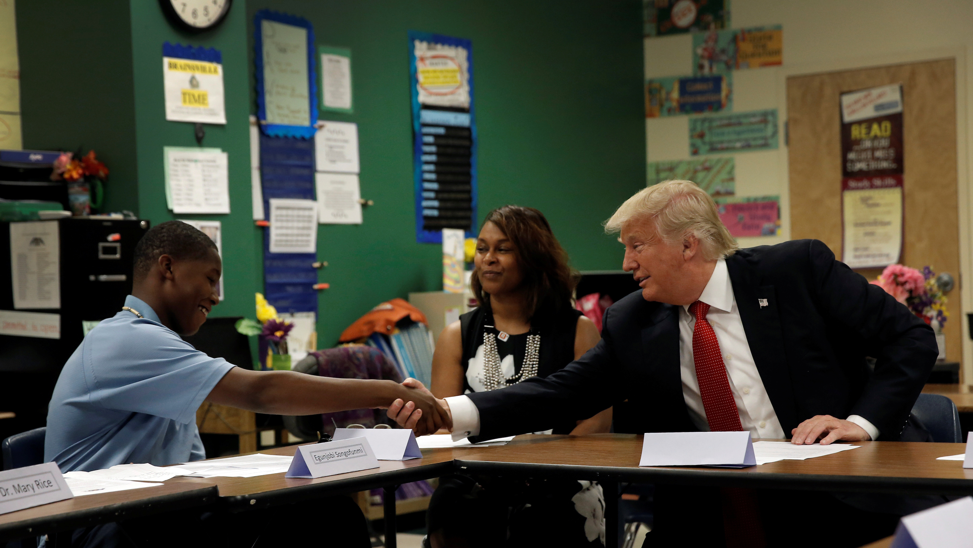 Republican presidential nominee Donald Trump shakes hands with 12 year old student Egunjobi Songofunmi during a campaign visit to Cleveland Arts and Social Sciences Academy in Cleveland, Ohio, U.S., September 8, 2016.  REUTERS/Mike Segar - RTX2OPK7
