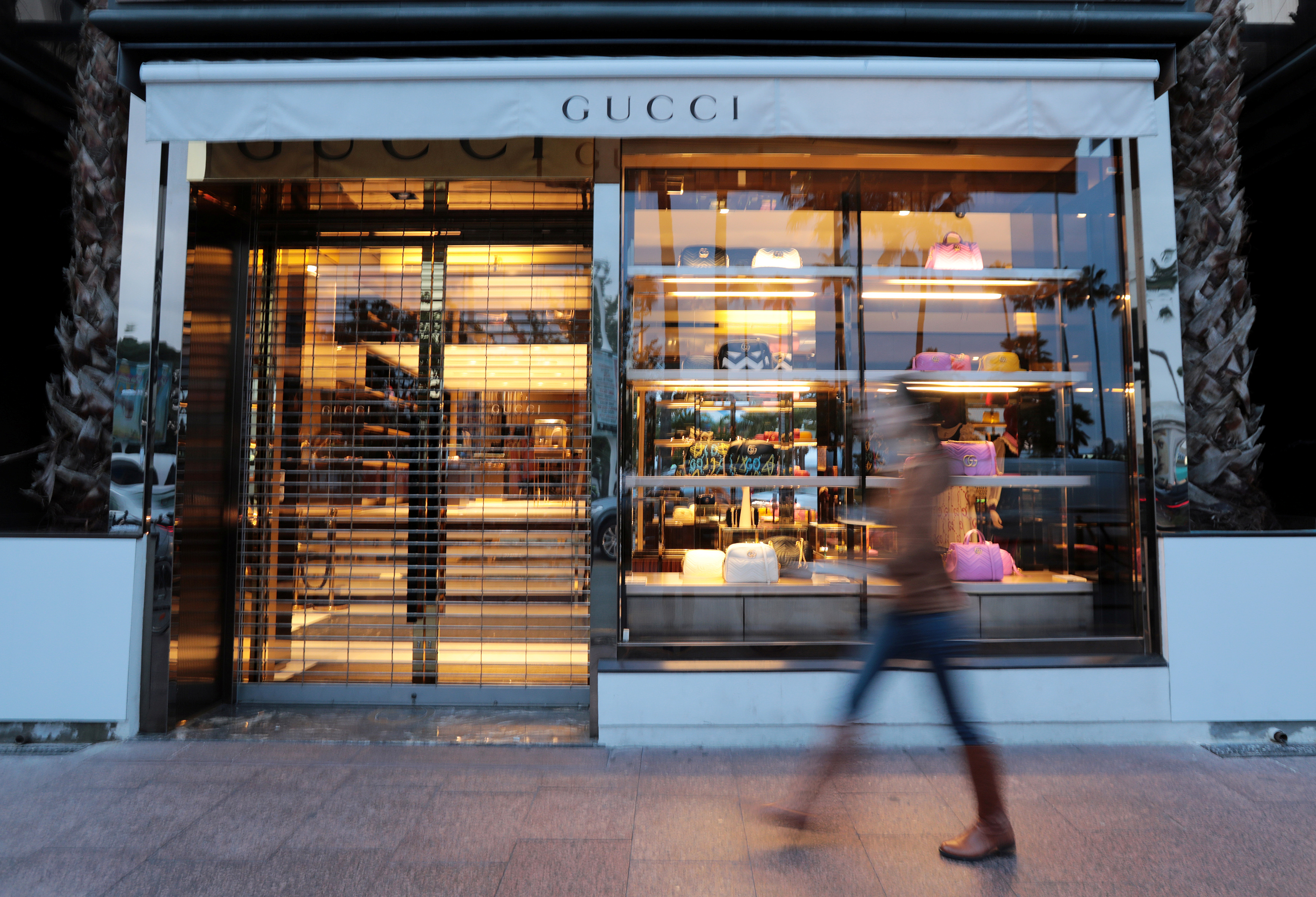 A woman walks past a store of Gucci brand in Cannes