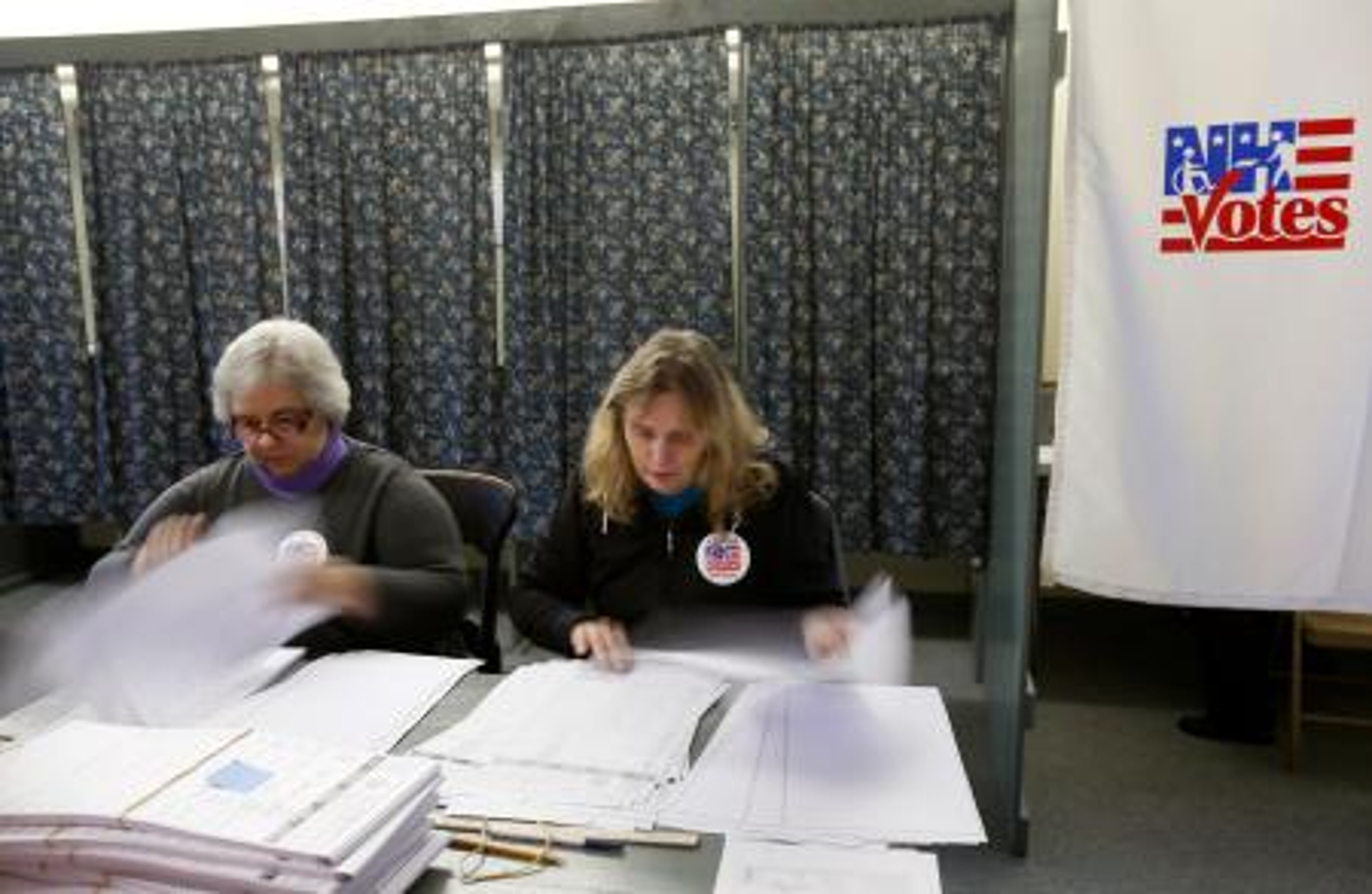 A woman sits reading ballots