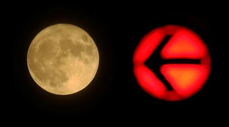 A red traffic light is seen next to the moon in downtown Frankfurt, Germany November 14, 2016.
