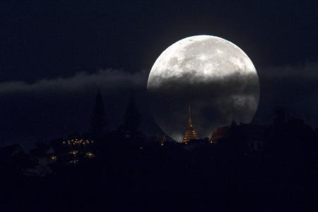 The supermoon is partly covered by clouds as it sets behind Wat Phrathat Doi Suthep in the northern capital of Chiang Mai, Thailand, November 15, 2016.