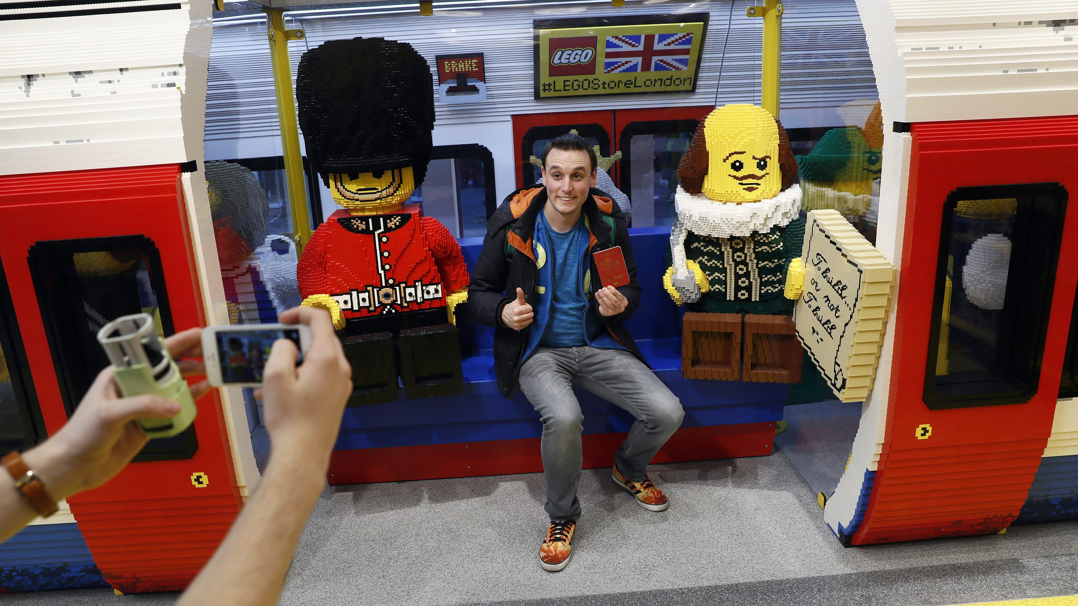 A man poses for a photograph in a Tube carriage made with Lego in the world's biggest Lego store in Leicester Square in London