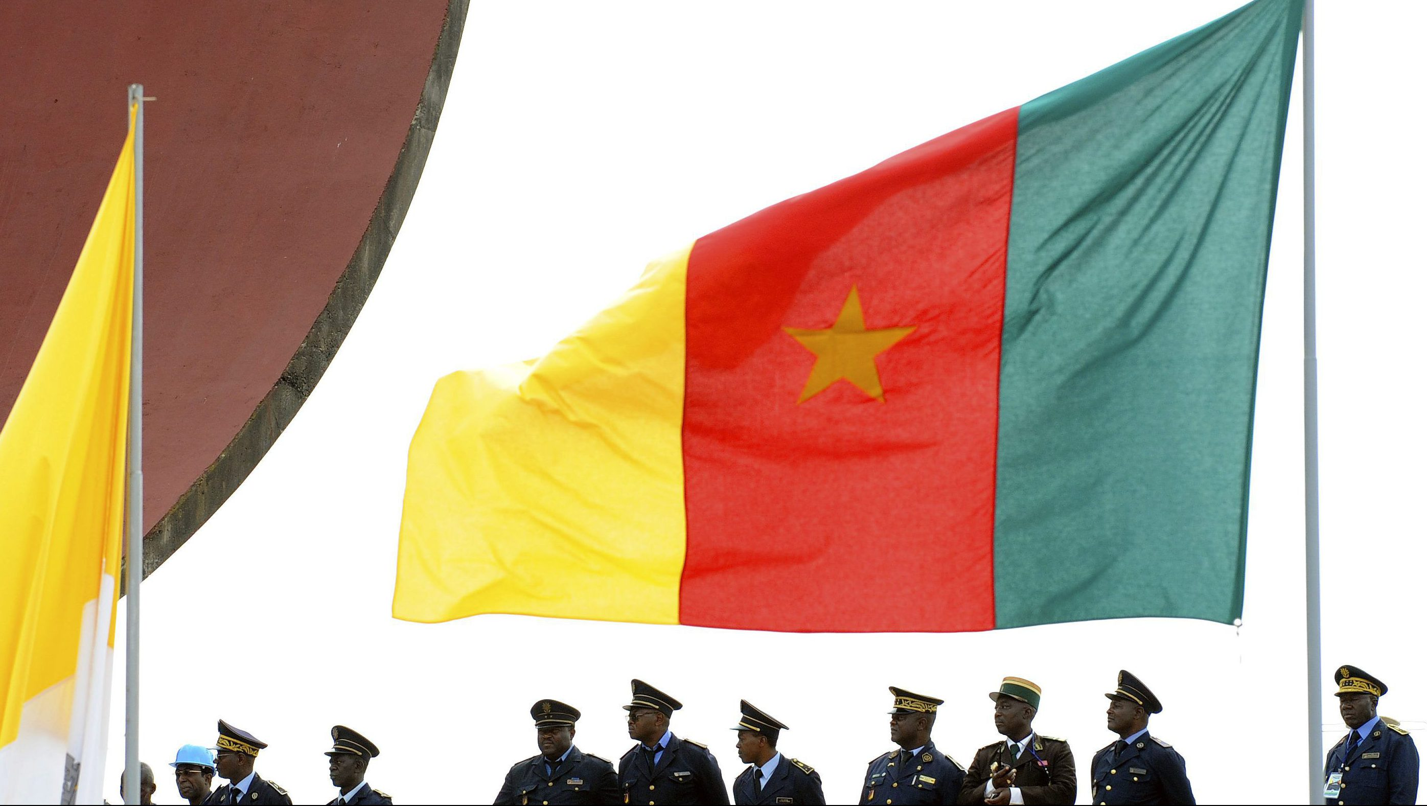 Cameroonian police stand near a national flag during a mass led by Pope Benedict XVI at Amadou Ahidjo stadium in Yaounde