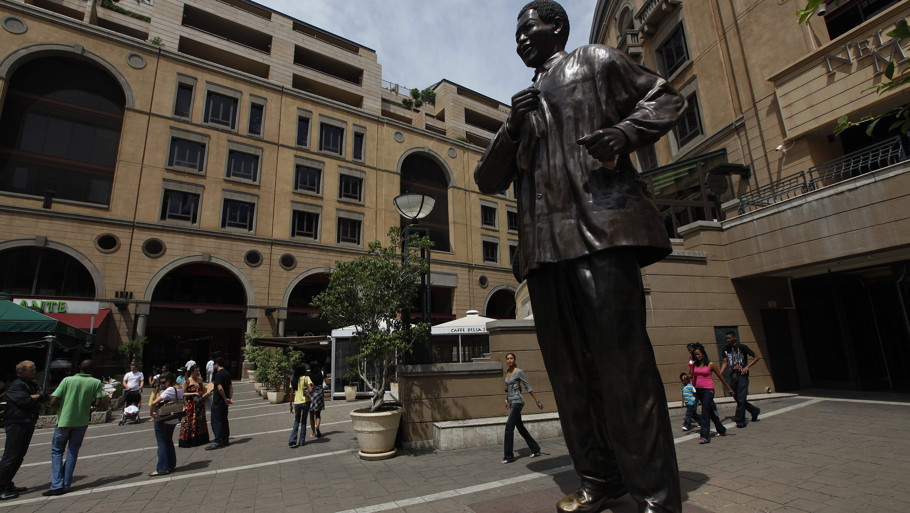Visitors walk past a statue of former President Nelson Mandela in Johannesburg's upmarket Sandton suburb