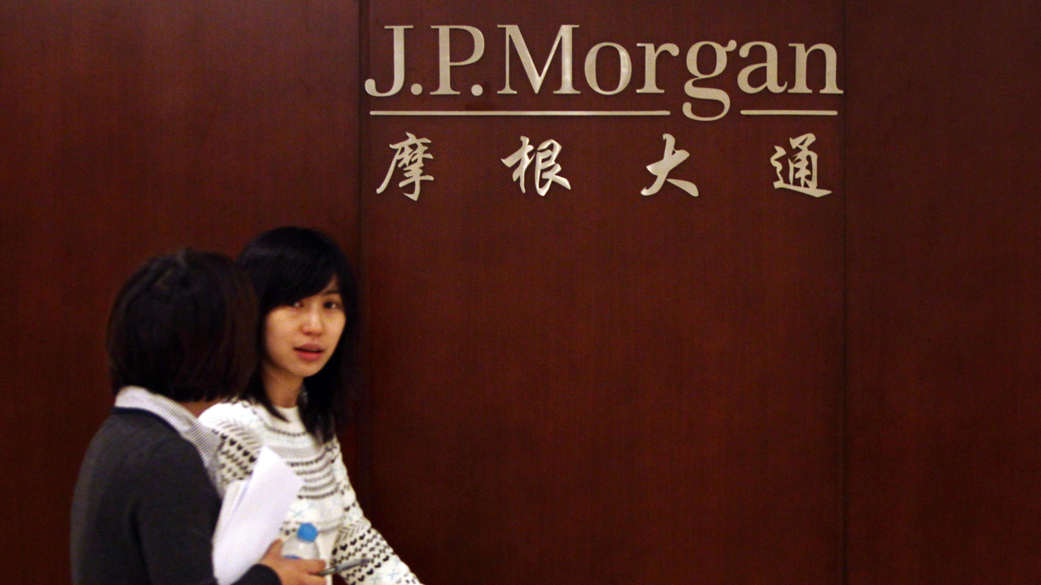 Employees walk past the company logo at the JPMorgan Beijing office in Beijing December 13, 2010. JPMorgan & Chase Co will see record revenues from China this year, as the second-largest U.S. bank benefits from a surge in equity raising by Chinese companies, the head of the bank's China investment banking business said on Monday at the Reuters China Investment Summit. REUTERS/Jason Lee(CHINA - Tags: BUSINESS) - RTXVOOH