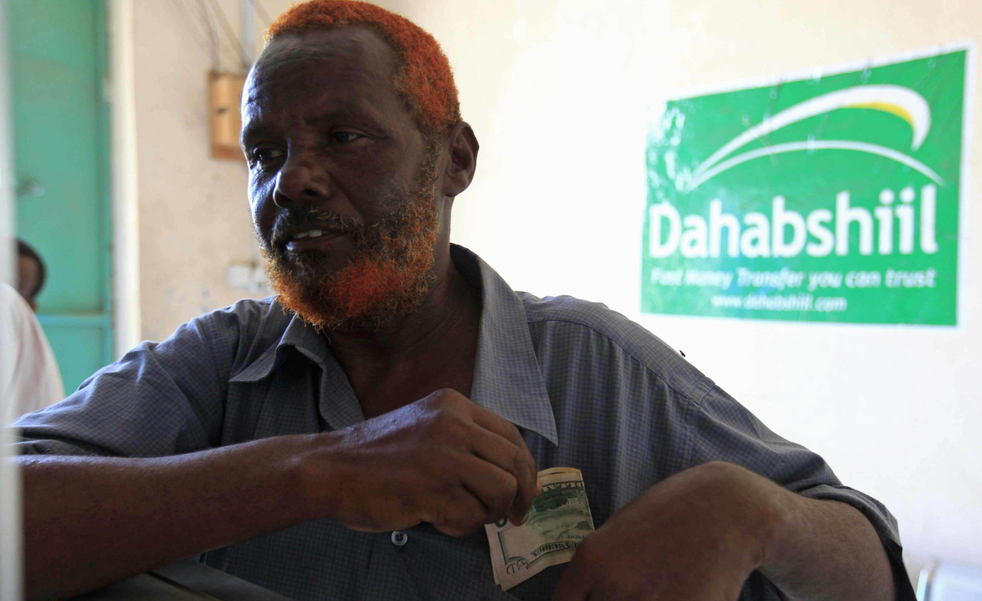 """A Somali man withdraws money from a Dahabshiil money transfer office in """"Kilometer Five"""" street of Soobe village, southern Mogadishu, May 8, 2013. Somalia's government must lure more investors to drive the private economy because business owners have an interest in cementing fragile security gains, the chief executive of Somalia's biggest financial firm said."""