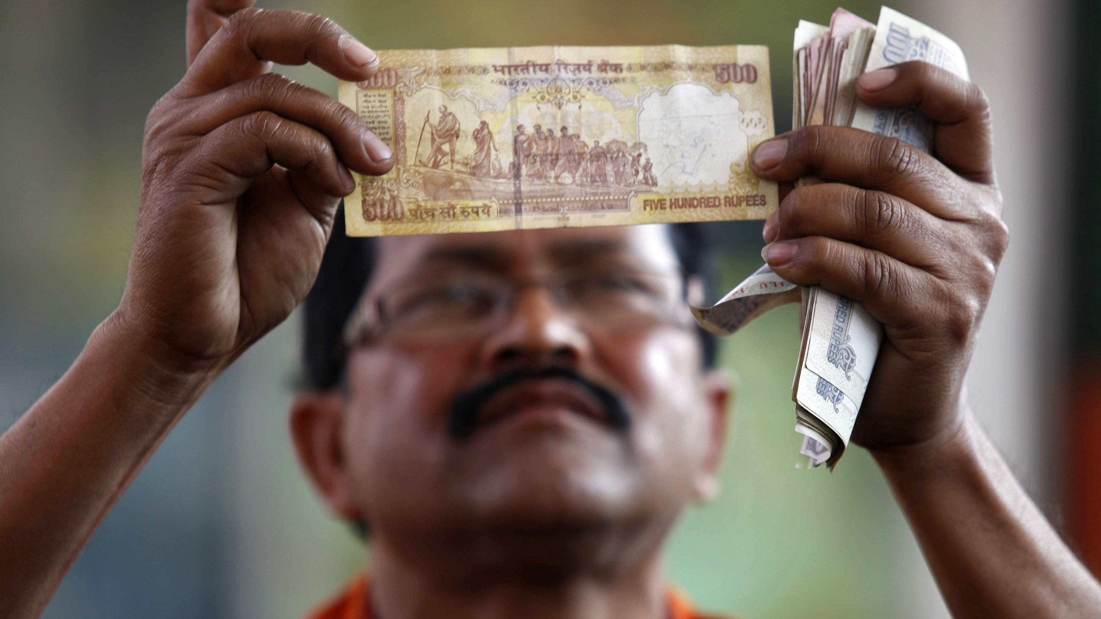 A worker at a fuel station checks a 500 Indian rupee note after filing a vehicle with fuel in Kolkata.