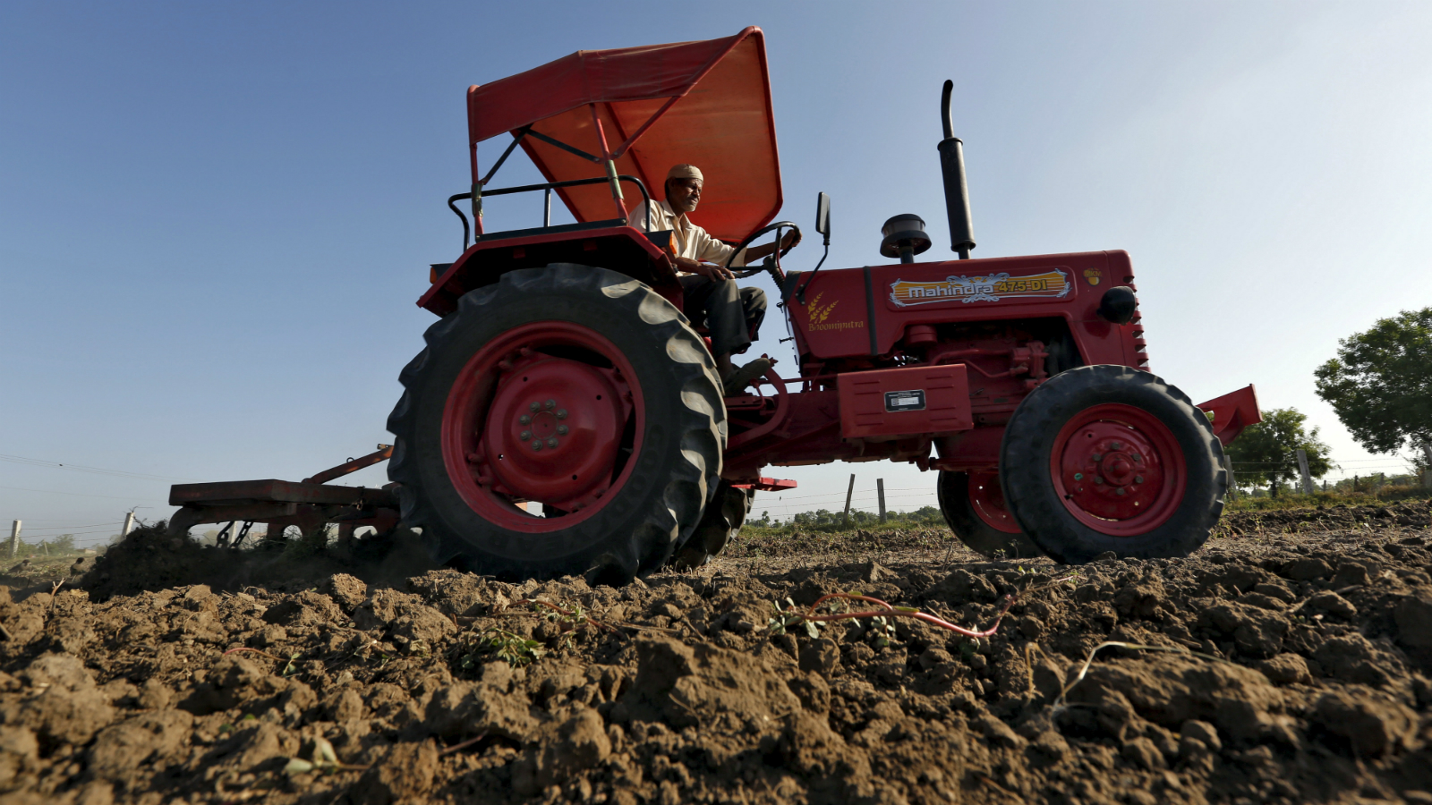 A farmer uses a tractor to plough his field before sowing rice seeds on the outskirts of Ahmedabad, India, in this June 10, 2015 picture. India's farm economy could contract this fiscal year for the first time in over a decade because of drought, threatening Prime Minister Narendra Modi's drive to lift millions in the countryside out of poverty and bolster his party's support.