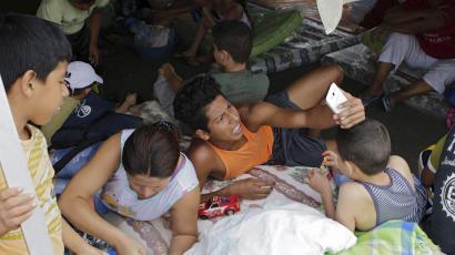 Residents take a selfie under a tent at the Reales Tamarindos airport, after being evacuated from their homes in Portoviejo, after an earthquake struck off Ecuador's Pacific coast