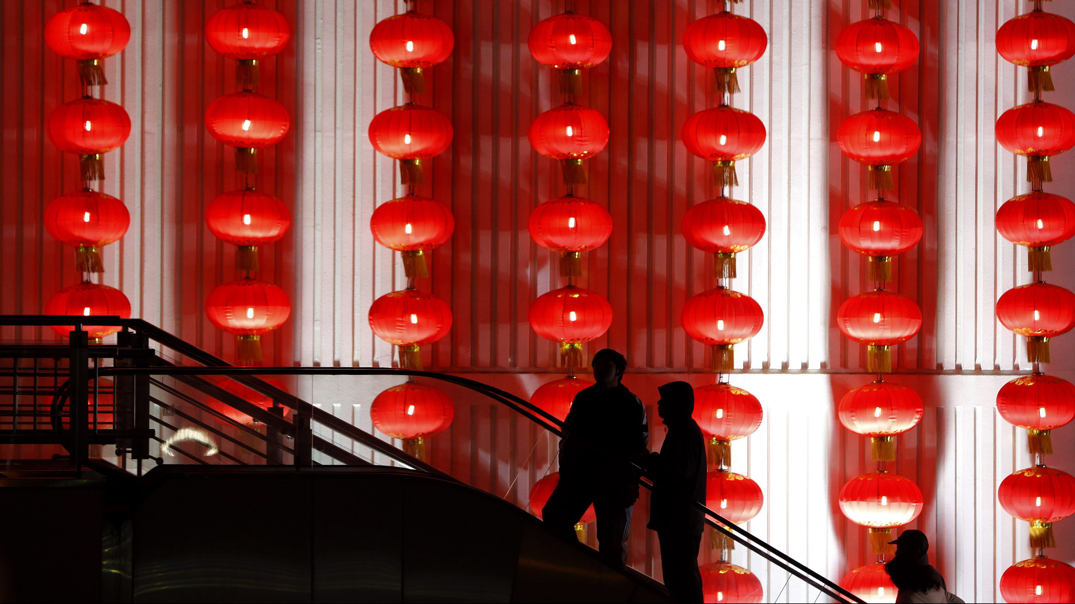 People walk past decorative red lanterns ahead of the New Year celebrations in Shanghai