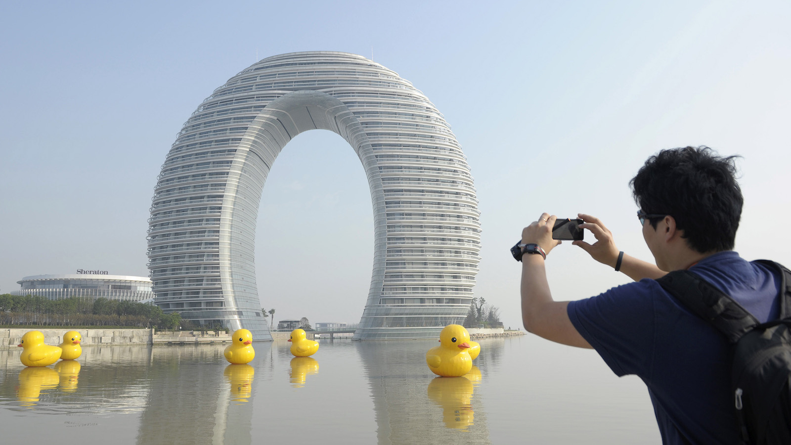 "A man takes pictures of the Sheraton Huzhou Hot Spring Resort, or ""Moon Hotel"", behind replicas of the rubber duck by Dutch conceptual artist Florentijn Hofman on Taihu Lake, in Huzhou, Jiangsu province November 6, 2013. The 27-storey luxury hotel, which was designed by Chinese architecture Ma Yansong, opened to the public in October 2013. The hotel is known in China by its nicknames such as ""Doughnut Hotel"" and ""Horseshoe Hotel"", local media reported. Picture taken November 6, 2013. REUTERS/Sean Yong (CHINA - Tags: SOCIETY TRAVEL) - RTX153NP"