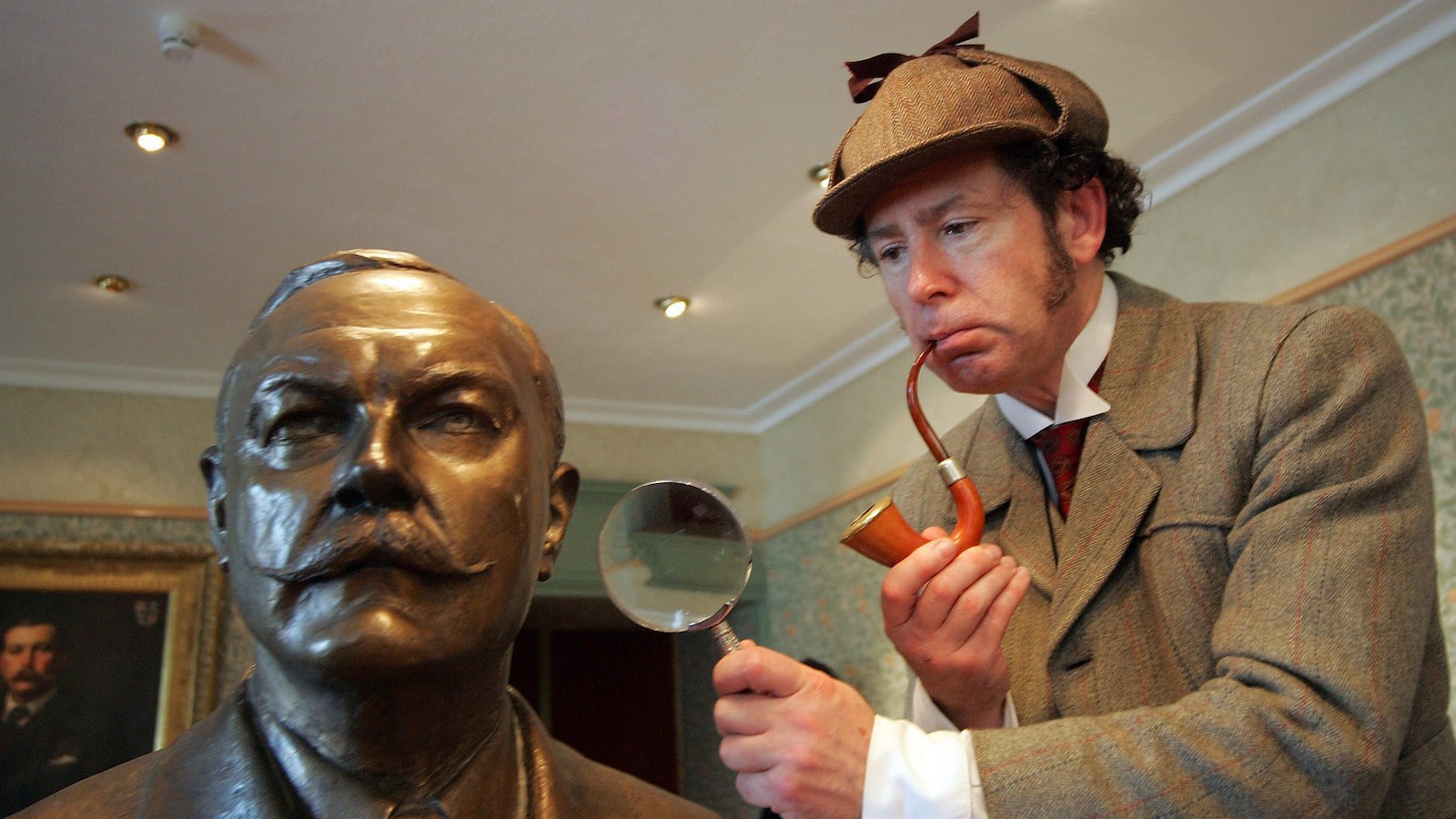 "Sherlock Holmes alias Philip Porter of the Sherlock Holmes Society of London takes a look at a statue of Arthur Conan Doyle at the Sherlock Holmes Museum in Lucens on Friday, June 17, 2005. The Sherlock Holmes Society of London is on a pilgrimage to Switzerland from June 15 to June 23. In accordance with tradition, the journey will follow the footsteps of Holmes in the book ""The Final Problem"", with a diversion in the Swiss Valais region. The members of the Society travel in late Victorian costumes. (AP Photo/Keystone, Photopress, Alessandro Della Bella)"