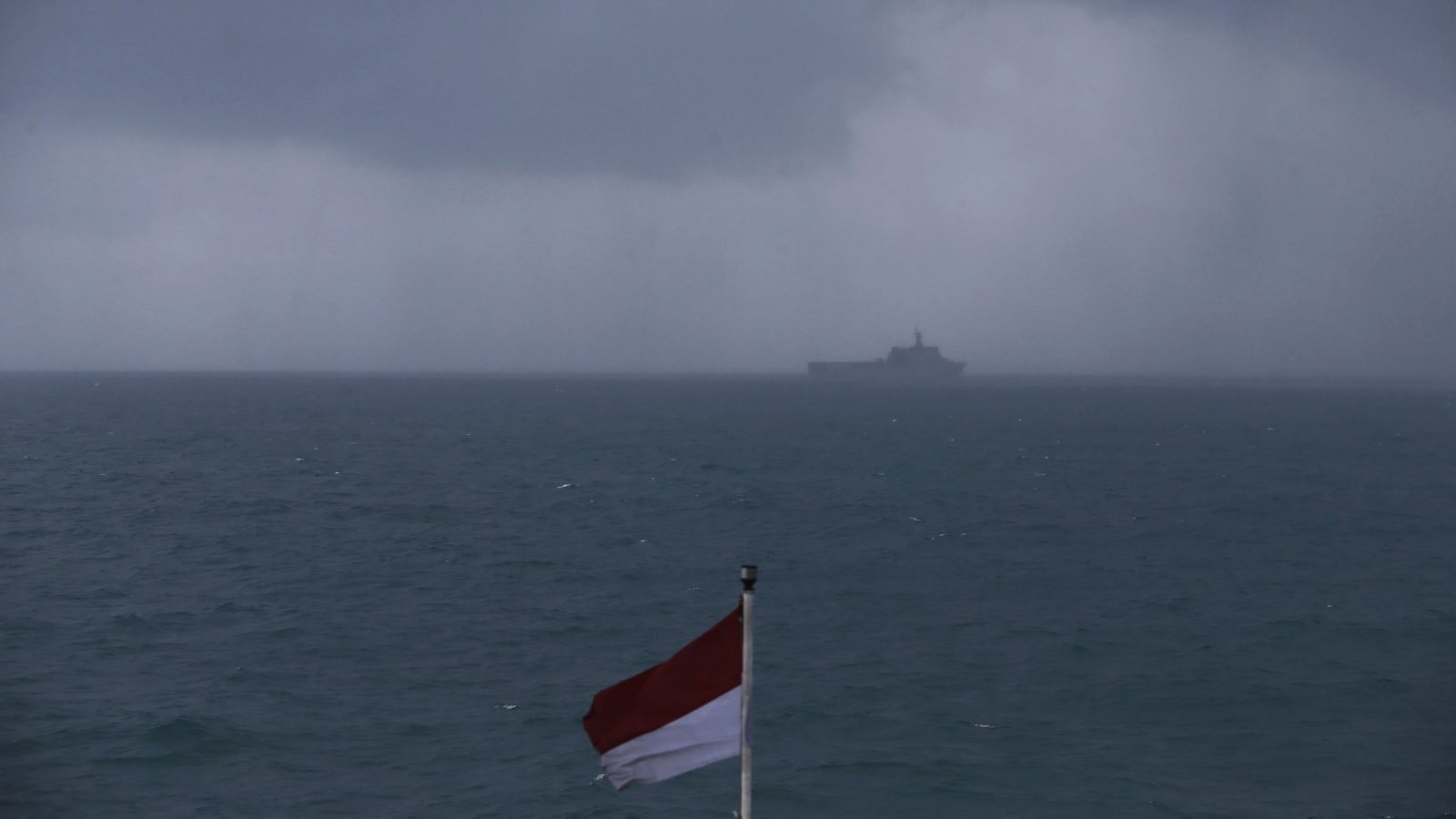 "The ship KRI Banda Aceh involved in a search operation for passengers onboard AirAsia Flight QZ8501 is seen on the horizon as dark clouds fill the sky, in the Java Sea January 4, 2015. Bad weather forced divers trying to identify sunken wreckage from the crashed AirAsia passenger jet to abort their mission on Sunday and Indonesian officials said they had not yet picked up any signals from the lost plane's ""black box"". The Airbus A320-200 crashed into the Java Sea about 40 minutes after taking off last Sunday from Indonesia's second-largest city Surabaya en route for Singapore. There were no survivors.     REUTERS/Beawiharta (INDONESIA - Tags: DISASTER ENVIRONMENT MARITIME TRANSPORT) - RTR4K0N7"