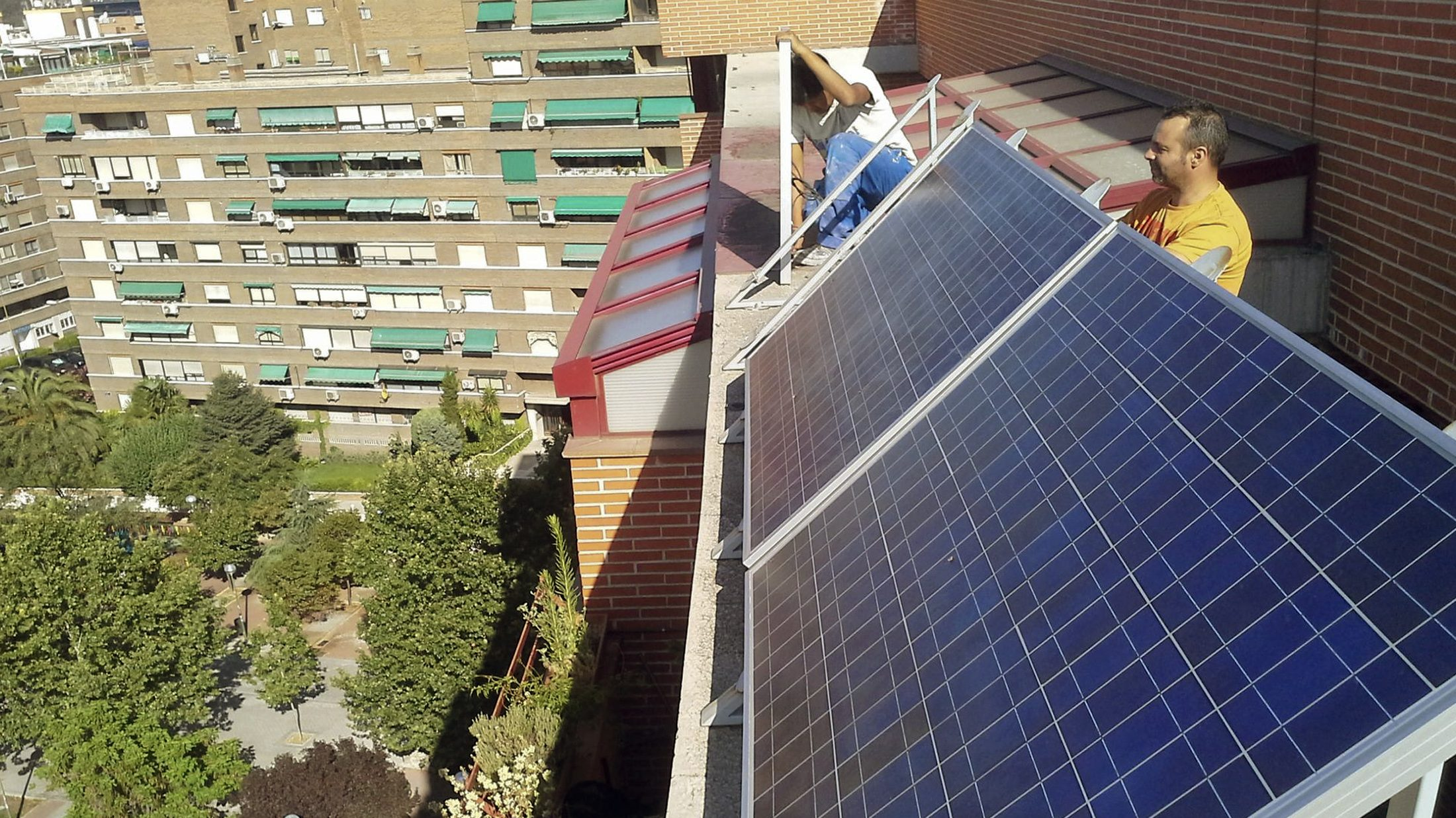 Workers remove solar panels from the roof of a building where Spanish ecological architect Inaki Alonso has his home in Madrid July 24, 2013. Two weeks after Spain's conservative government unveiled a sweeping energy reform with levies on green energy, Alonso hired two men to take down the roof-top solar panels he had put up six months earlier. Calculating the cost of using solar panels after a new government levy that will make it more expensive to generate your own energy, Alonso - an ecological architect - said the numbers did not add up. And by keeping the panels without connecting them to the electricity grid as mandated in a new energy law, Alonso faced a government fine of between 6 million and 30 million euros ($8 million-$40 million). Picture taken July 24, 2013.