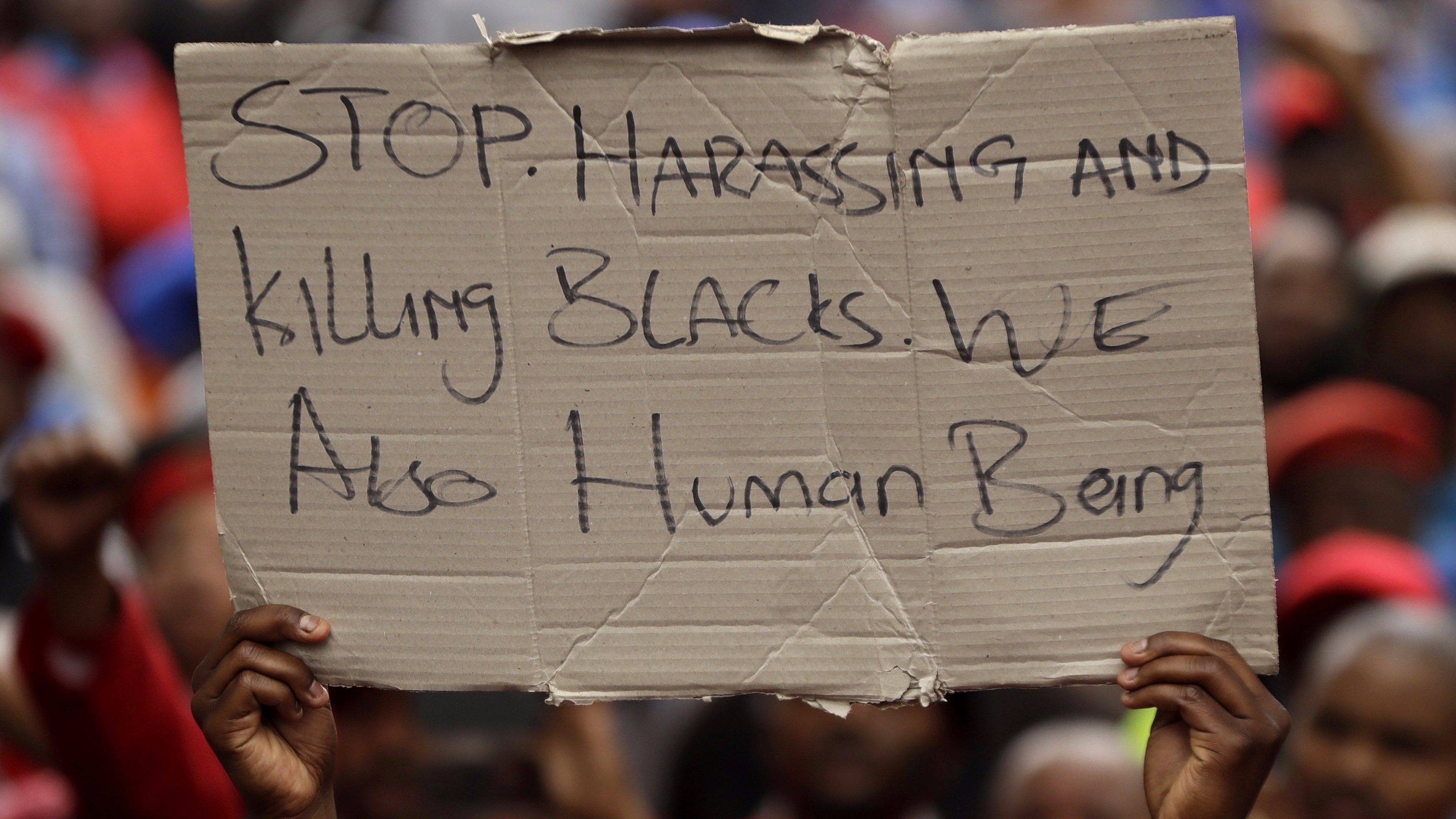 Economic Freedom Fighters (EFF), supporter holds a placard outside the court in Middelburg, South Africa, 16, 2016. Demonstrators, protesting against racism outside a South African courthouse where two white men face assault charges for allegedly forcing a black man into a coffin and threatening to set him on fire. (AP Photo/Themba Hadebe)