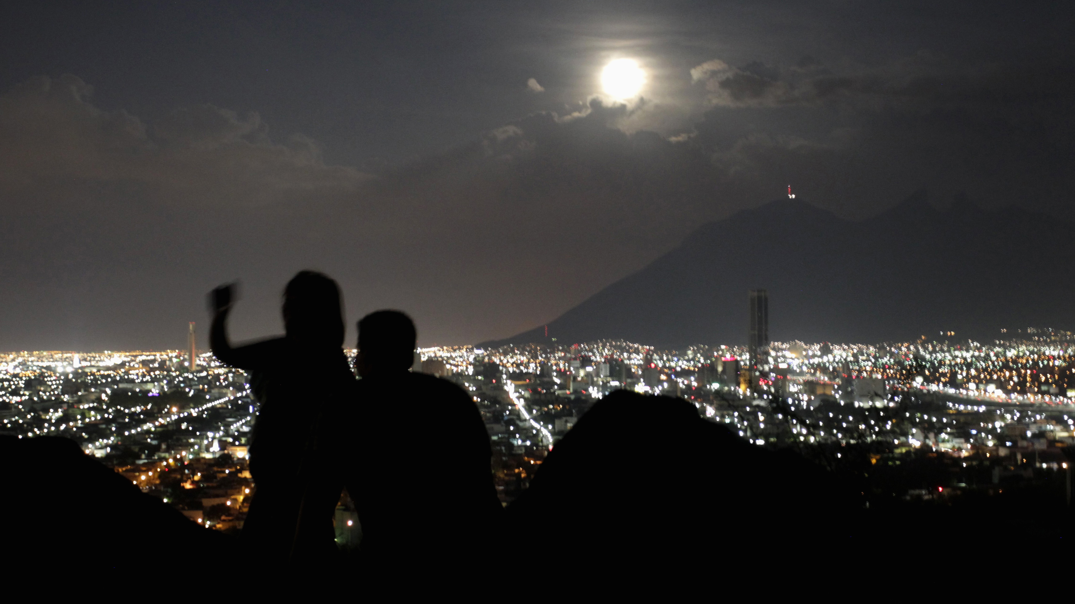 A supermoon rises while a couple takes a photo in Monterrey August 10, 2014. The astronomical event occurs when the moon is closest to the Earth in its orbit, making it appear much larger and brighter than usual. Reuters/Daniel Becerril (MEXICO - Tags: ENVIRONMENT SOCIETY TPX IMAGES OF THE DAY) - RTR41X1E