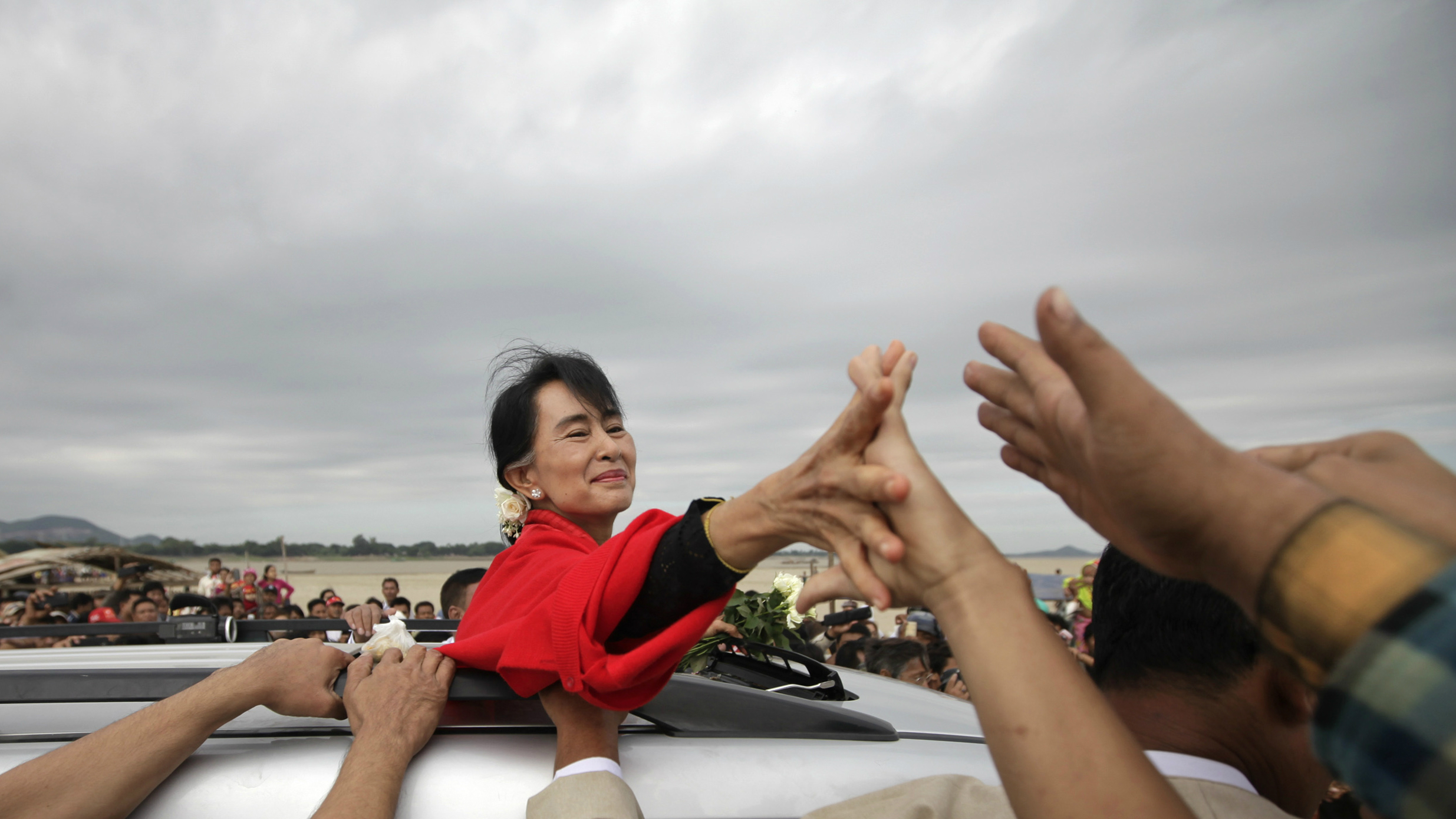 Myanmar pro-democracy leader Aung San Suu Kyi shakes hands with supporters after giving a speech in Monywa November 30, 2012. Suu Kyi offered to mediate between company officials and those who are opposing a vast copper mining project after riot police fired water cannon and tear gas on Thursday to break up a three-month protest against the project run by the powerful Myanmar military and its partner, a subsidiary of a Chinese arms manufacturer. Activists said at least 50 people had been injured and 23 were in hospital, some suffering burns after incendiary devices were hurled into their camps by police.