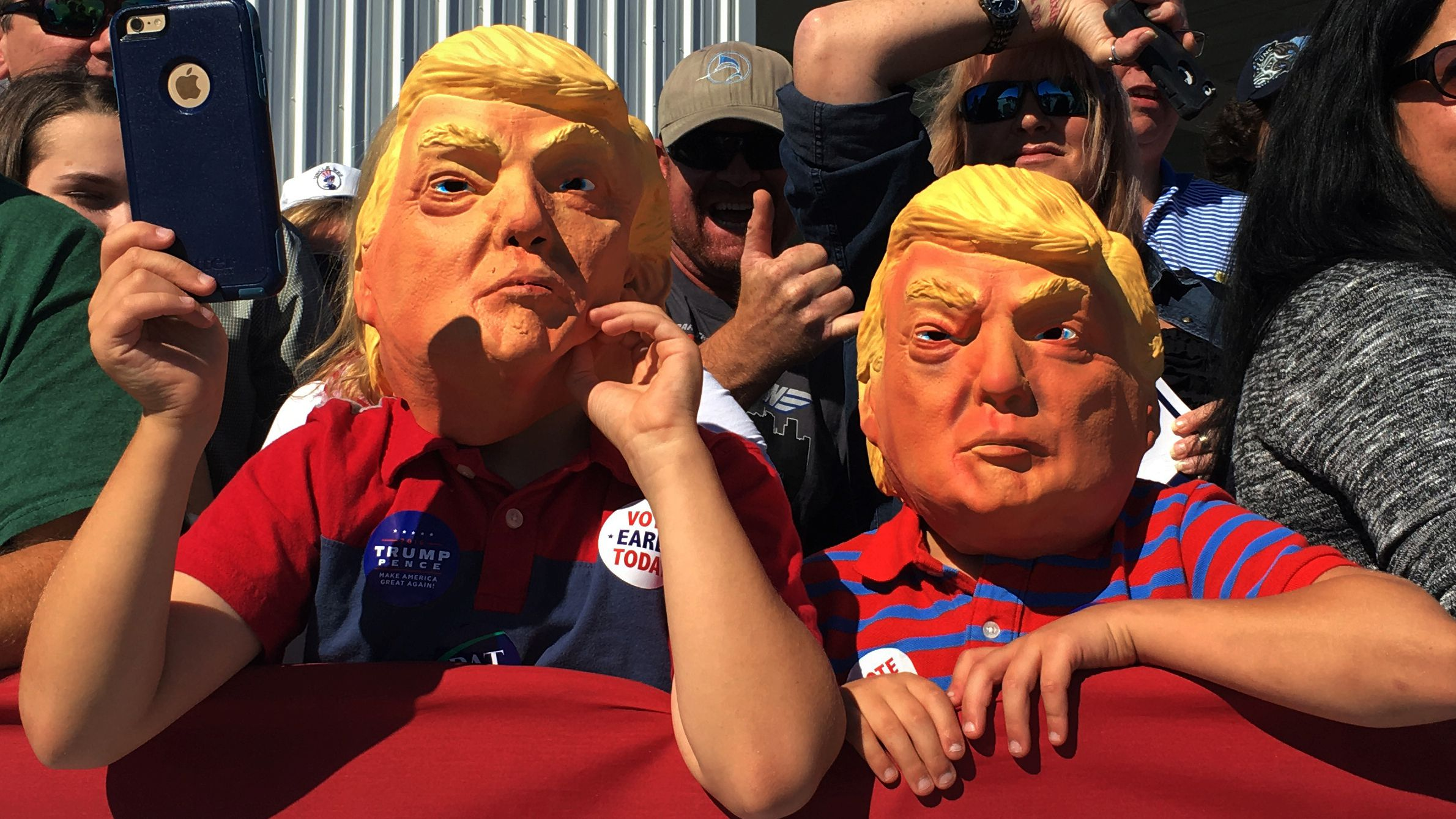 Children wearing masks wait for Republican presidential nominee Donald Trump to hold a campaign rally.