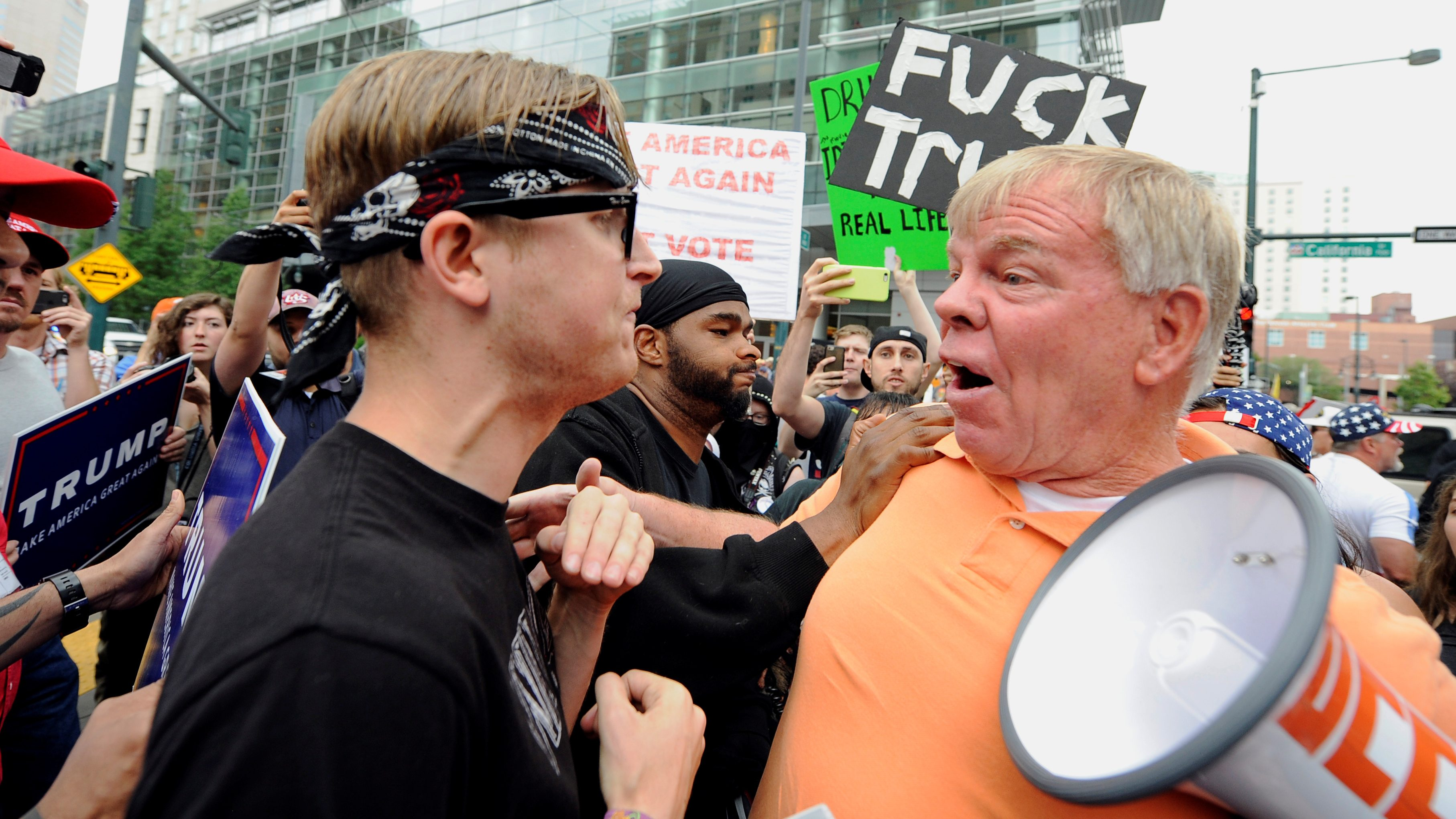 An unidentified anti-Trump protestor (L) and an unidentified Trump supporter (R) get into a scuffle outside the venue where U.S. Republican presidential candidate Donald Trump was speaking in downtown Denver, U.S. July 1, 2016.