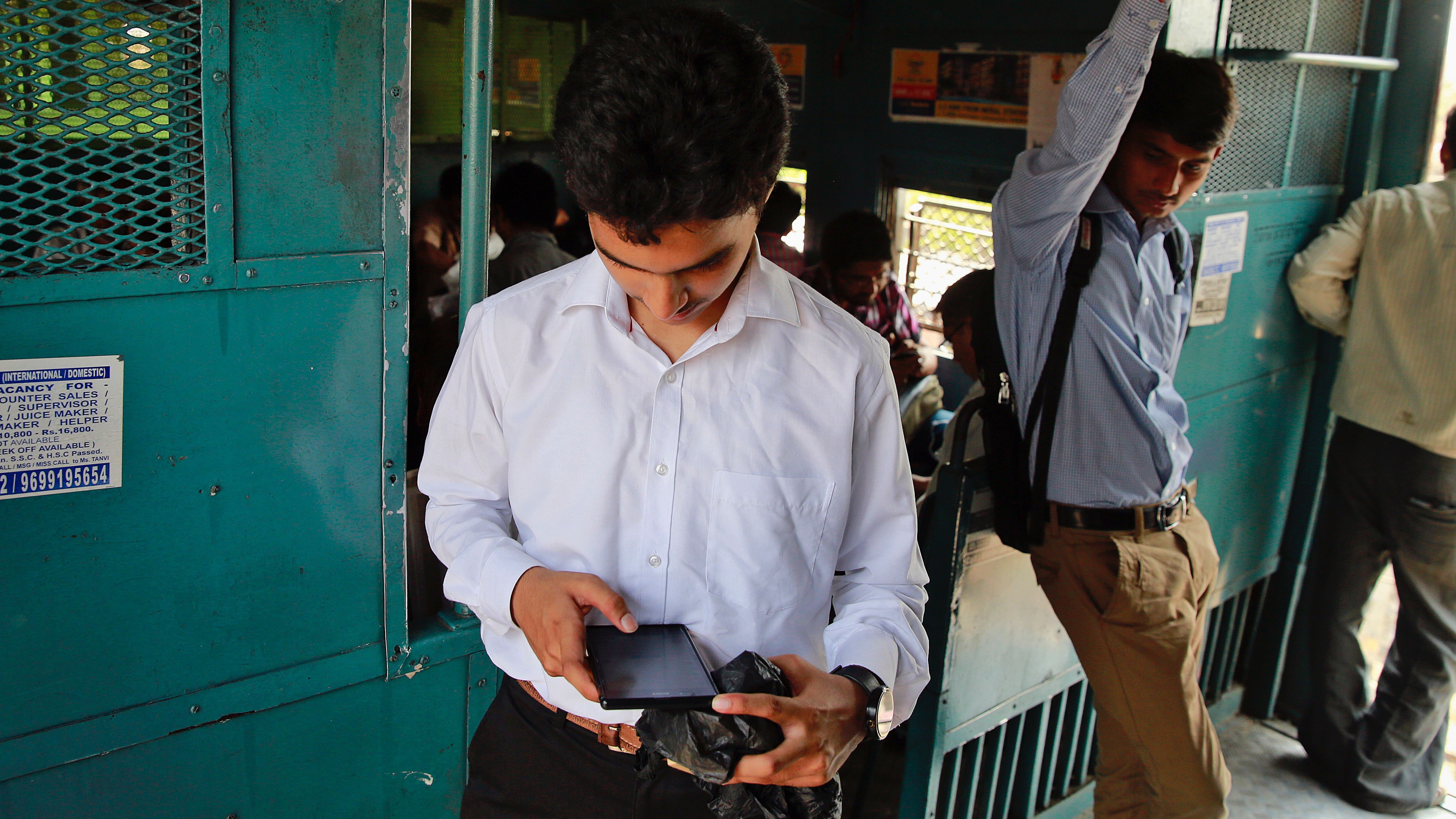 """An Indian man surfs the internet on his smartphone as he travels in a local train in Mumbai, India, Tuesday, March 24, 2015. India's top court affirmed people's right to free speech in cyberspace Tuesday by striking down a provision that had called for imprisoning people who send """"offensive"""" messages by computer or cellphone.The provision, known as Section 66A of the 2008 Information Technology Act, had made sending such messages a crime punishable by up to three years in prison. (AP Photo/Rafiq Maqbool)"""