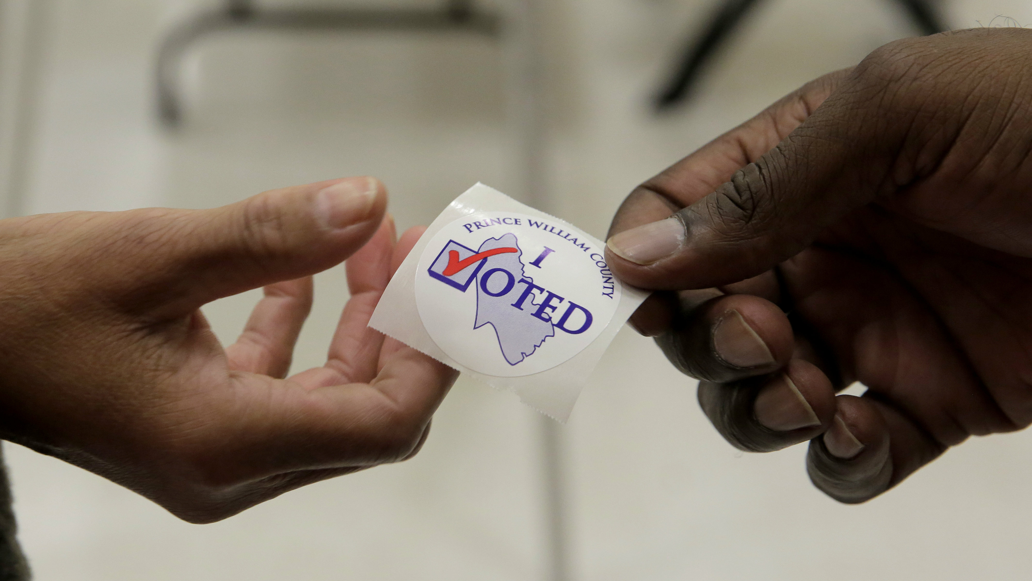 "A poll worker hands out an ""I voted"" sticker to a voter during the U.S. presidential election at Potomac Middle School in Dumfries, Virginia."