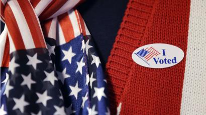 A close-up image of a person in a red vest and star-spangled scarf with an 'I Voted' sticker.