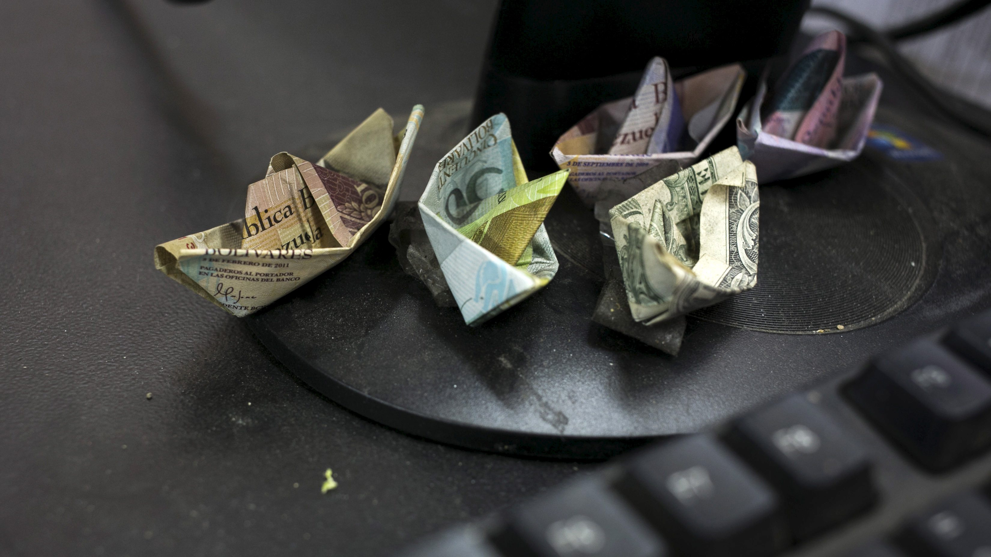 Venezuelan bolivar banknotes and a U.S. dollar banknote, folded as boats, are seen at a fruit and vegetable store in Caracas July 10, 2015. Origami-like boats made from Venezuela's rapidly depreciating bolivar bills sit on the cash register of the small fruit and vegetable store in Caracas. Cashier Marisol Garcia makes the bolivar boats to illustrate roaring inflation and the currency's tumble on the black market, where even the country's biggest bill is worth just 16 U.S. cents.