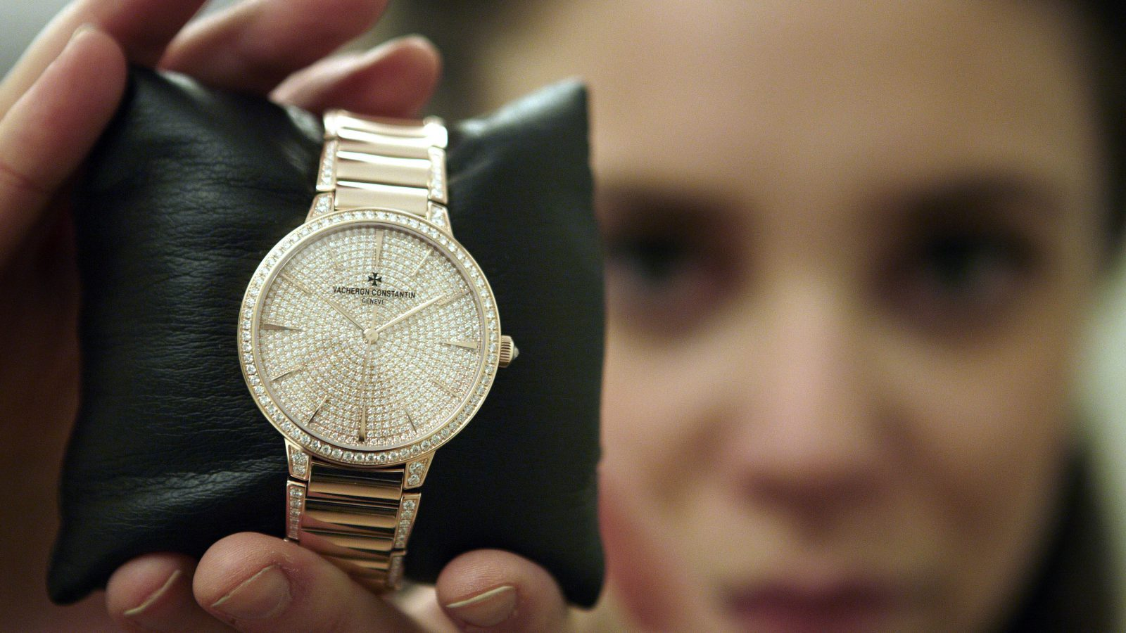 """A member of staff holds a Vacheron Constantin golden watch made with 778 diamonds at the """"Salon International de la Haute Horlogerie"""" SIHH exhibition at the Palexpo in Geneva January 21, 2013. Some 16 brands of watches and jewellery, part of the Richemont group, are exhibiting their new models from January 21 to 25, 2013. REUTERS/Denis Balibouse (SWITZERLAND - Tags: BUSINESS SOCIETY) - RTR3CQVL"""