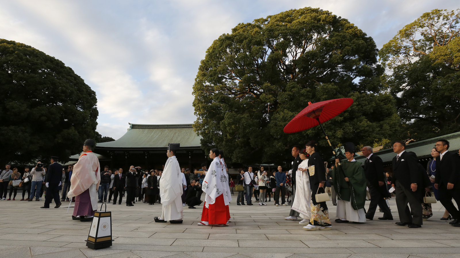 A newlywed couple, fourth and fifth from left, are escorted by a Shinto priest at Meiji Jingu Shrine during a Japanese traditional wedding ceremony in Tokyo, Monday, Nov. 3, 2014. (AP Photo/Shizuo Kambayashi)