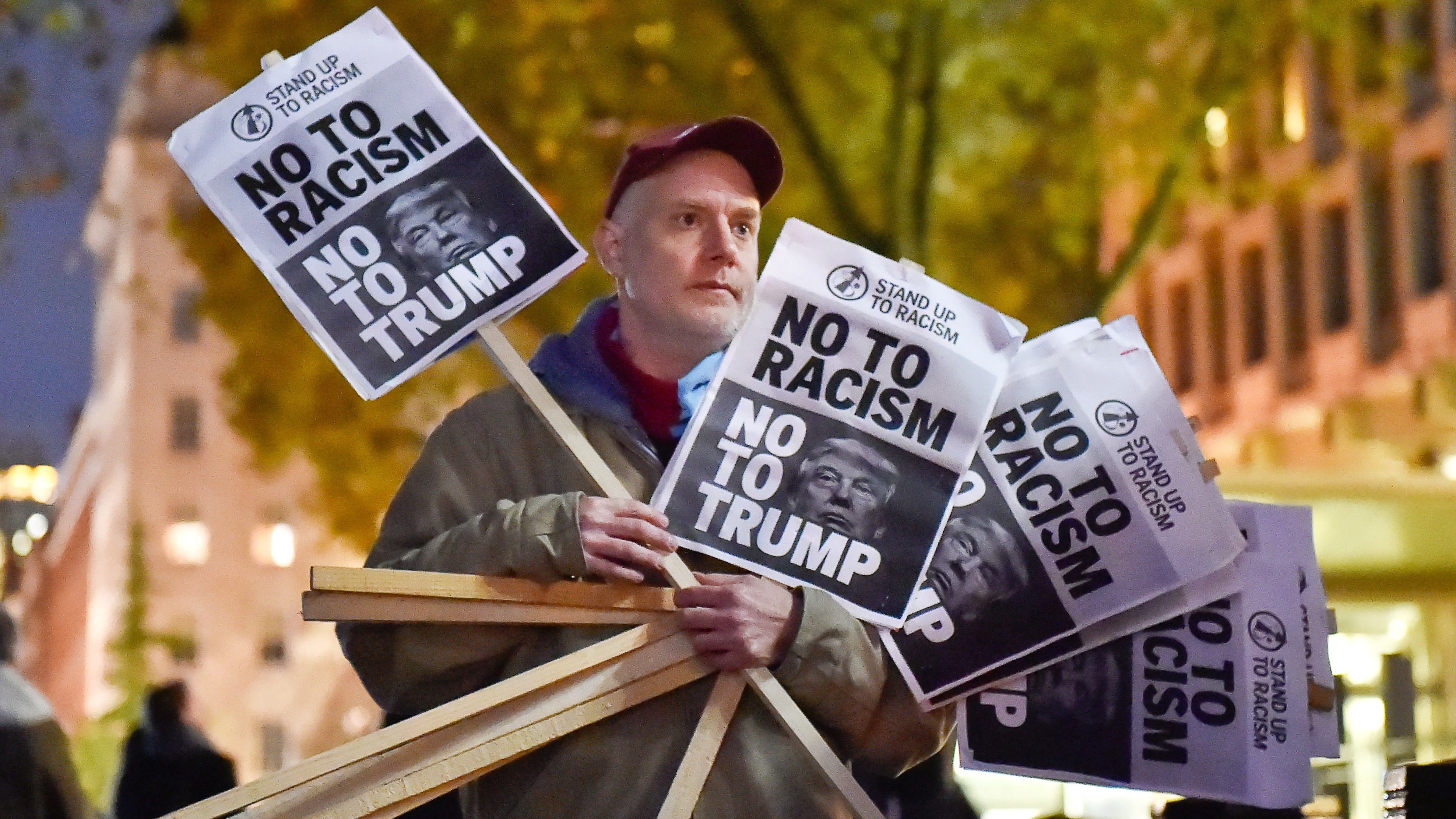 A man holds placards at an anti-racism protest against U.S. President-elect Donald Trump outside of the U.S Embassy in London, Britain, November 9, 2016. REUTERS/Hannah McKay - RTX2SW46