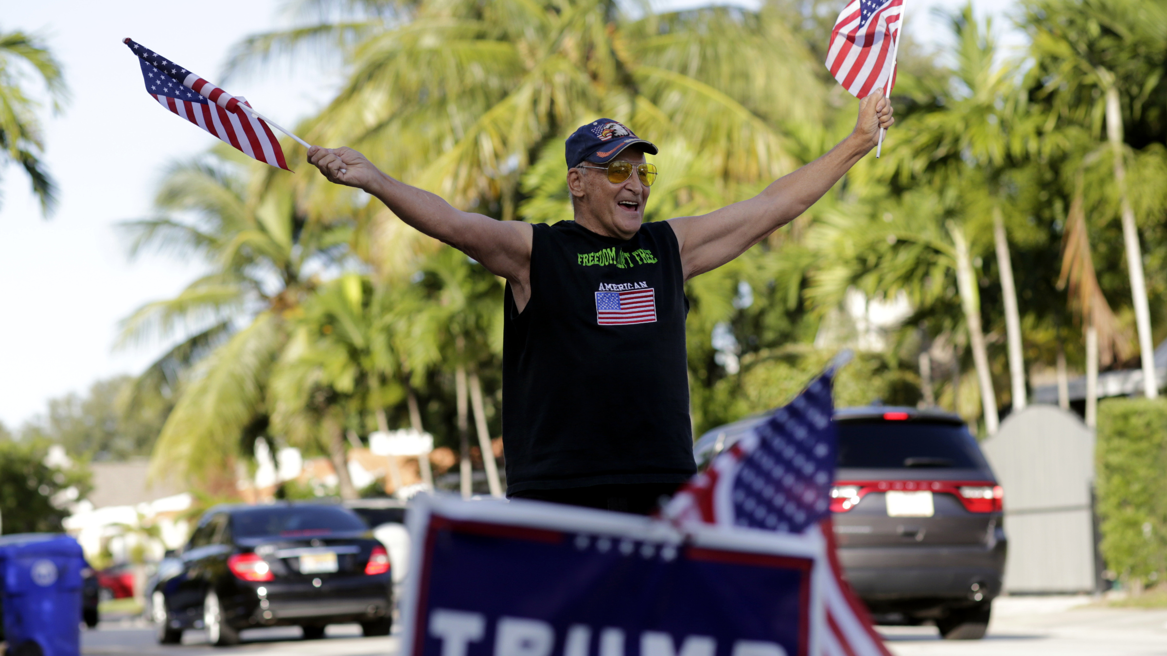 Peter Knapp, a supporter of Republican candidate Donald Trump, waves American flags as he stands outside his home on Election Day, Tuesday, Nov. 8, 2016, in Miami.
