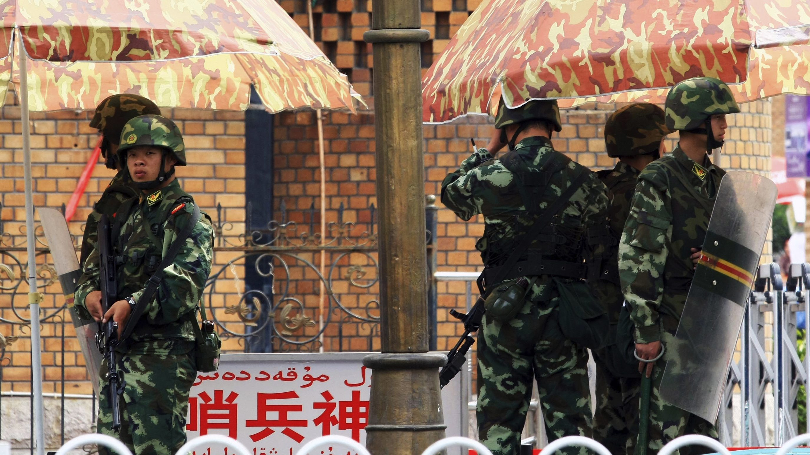 Armed paramilitary policemen stand on duty in downtown Urumqi, Xinjiang Uighur autonomous region, August 24, 2009. China is likely to begin trials this week over deadly riots in the restive far-west region of Xinjiang last month, with hundreds facing murder, arson and other charges, the official China Daily said. Picture taken August 24, 2009. REUTERS/China Daily (CHINA POLITICS CRIME LAW SOCIETY) CHINA OUT. NO COMMERCIAL OR EDITORIAL SALES IN CHINA - RTR2730D