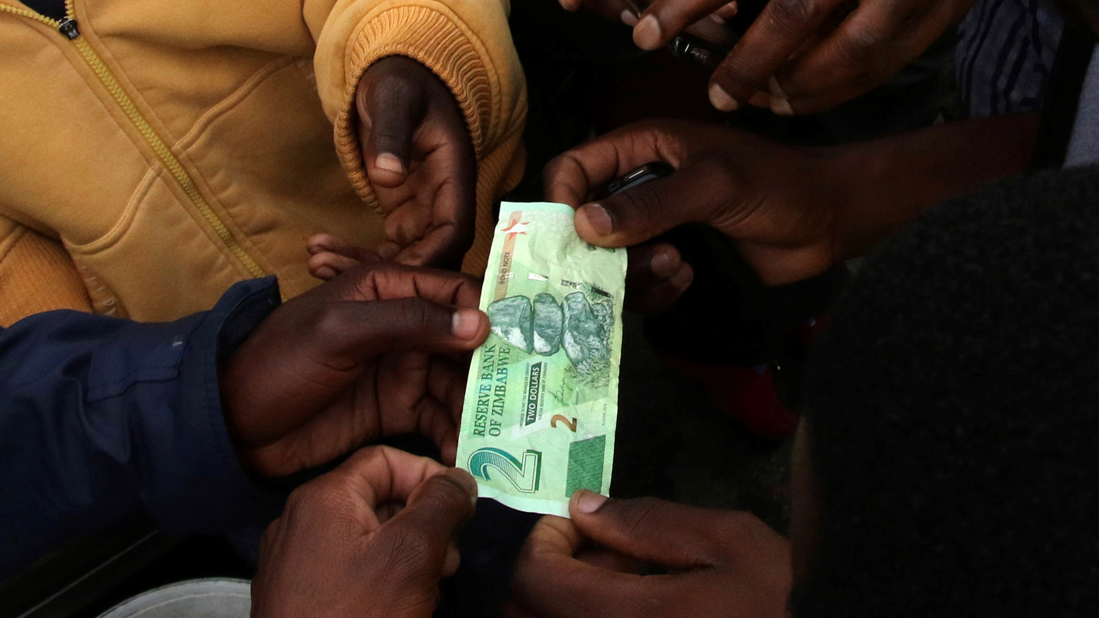 Illegal money changers having a feel of the new bond note in the capital Harare, Zimbabwe, November 28,2016.REUTERS/Philimon Bulawayo - RTSTMAE