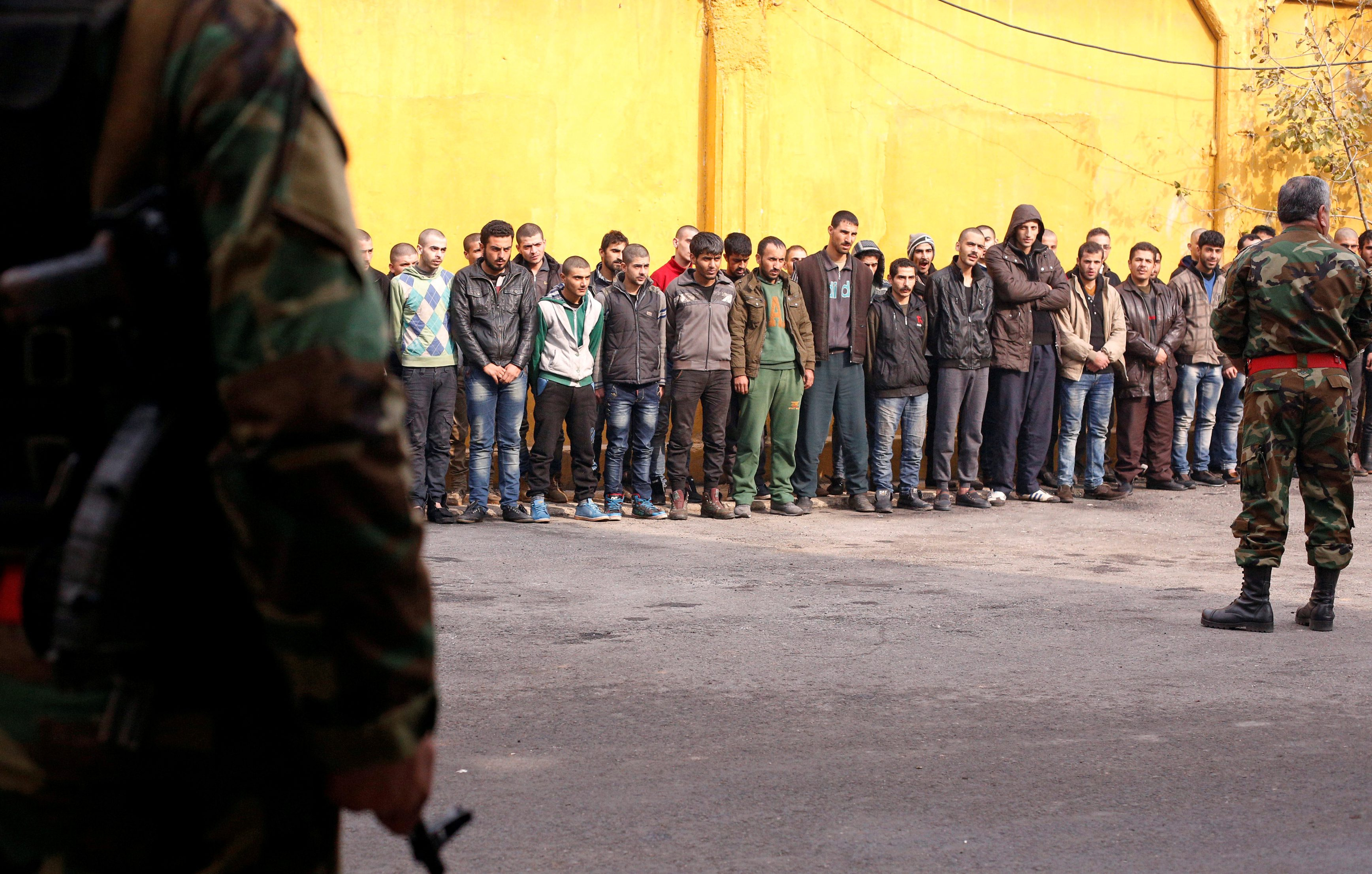Members of government military police stand guard as men, who were evacuated from the eastern districts of Aleppo, are being prepared to begin their military service at a police centre in Aleppo, Syria December 11, 2016.