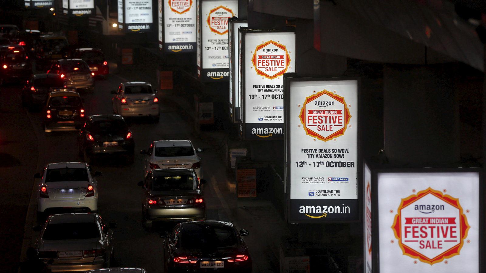 Traffic moves on a road past advertisements of Indian online marketplace Amazon, in Mumbai, India, October 15, 2015. Amazon.com could emerge as the biggest winner from one of India's most important festive - and shopping - seasons that began this week, after the e-tailer offered steep discounts, swift delivery and even gold bars to grab market share. The month-long festive season culminates around November 10 in Diwali, or the Festival of Lights, but the first nine days are considered an especially auspicious time to make big purchases. Picture taken October 15, 2015.