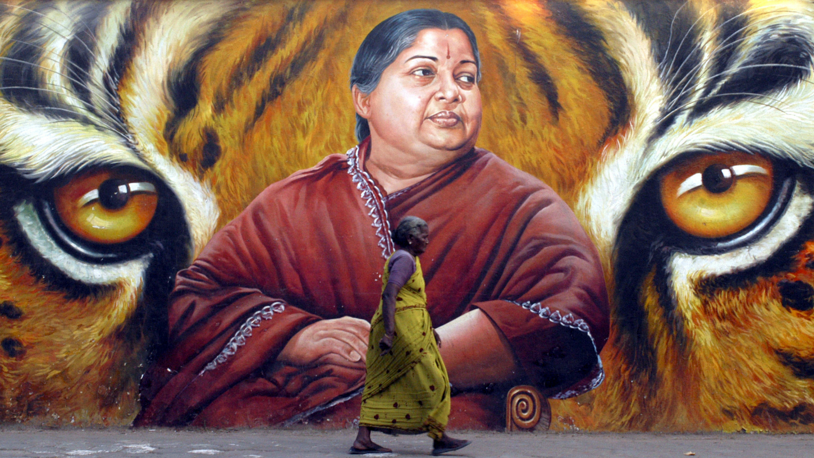 A woman walks in front of a portrait of Jayalalithaa, a former film actress and now head of the state opposition party, the All India Anna Dravida Munnetra Kazhagam (AIADMK), in the southern Indian city of Chennai March 2, 2009. India will hold a general election between April 16 and May 13, election officials said on Monday, kicking off a mammoth process in which 714 million people will be able to cast their votes.