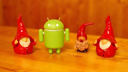 Google's Android mascot with Santa Claus figurines.