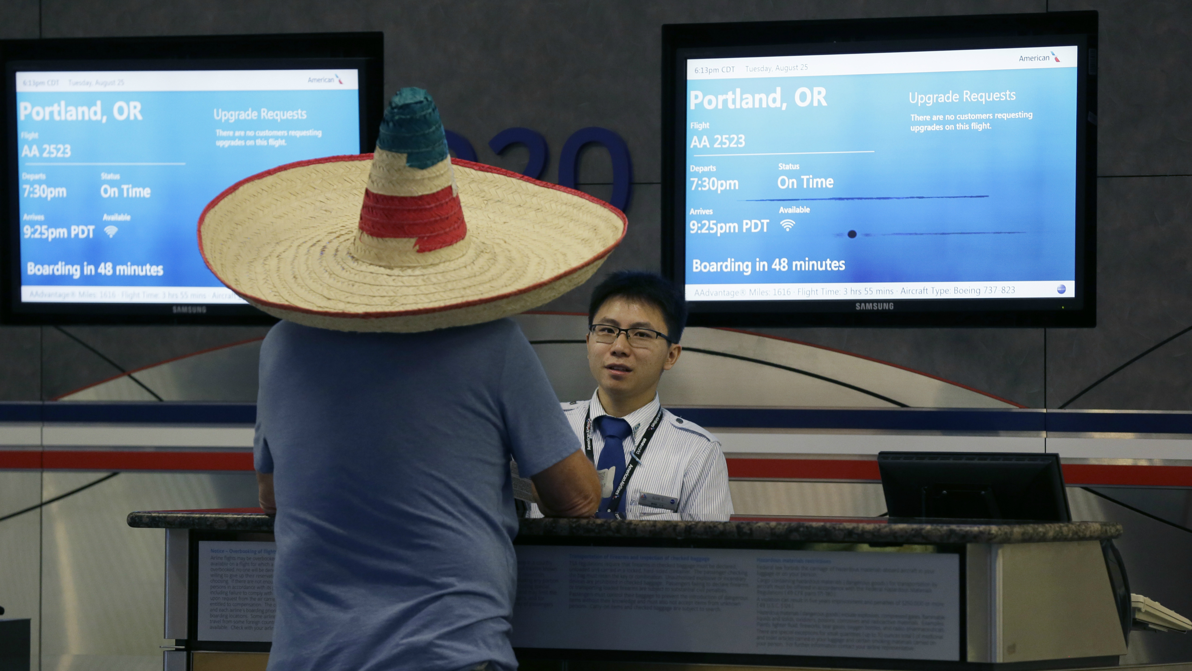Man wearing sombrero checking in to a flight.