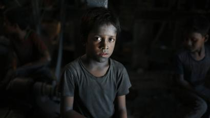 In this Sunday, June 12, 2016, photo, Ridoy, 7, poses for a portrait as he works at a factory that makes metal utensils in Dhaka, Bangladesh. The World Day Against Child Labor, which was initiated in 2002 by the International Labor Organization to highlight the plight of child laborers, is observed across the world on June 12. (AP Photo/A.M. Ahad)