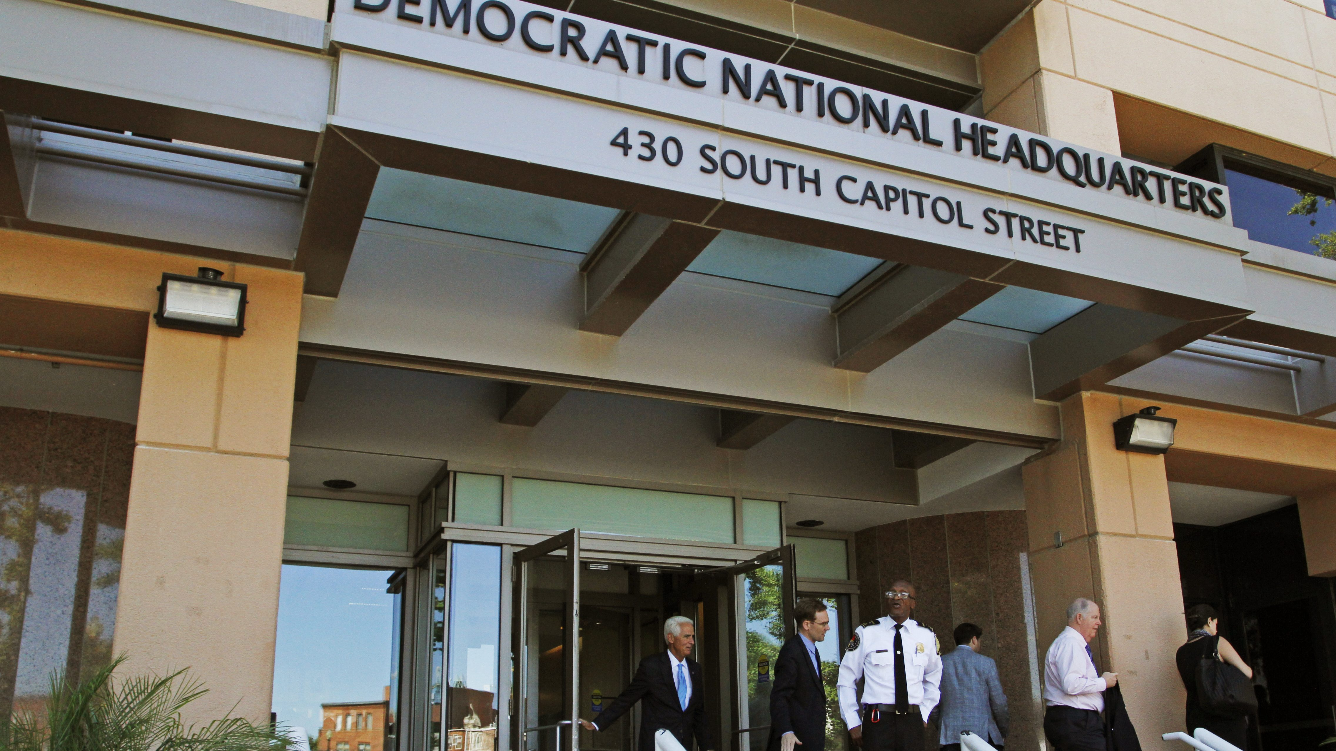 """People stand outside the Democratic National Committee (DNC) headquarters in Washington, Tuesday, June 14, 2016. Two """"sophisticated adversaries"""" linked to Russian intelligence services broke into the Democratic National Committee's computer networks and gained access to confidential emails, chats and opposition research on presumptive Republican nominee Donald Trump, the party and an outside analyst said Tuesday, June 14, 2016. (AP Photo/Paul Holston)"""