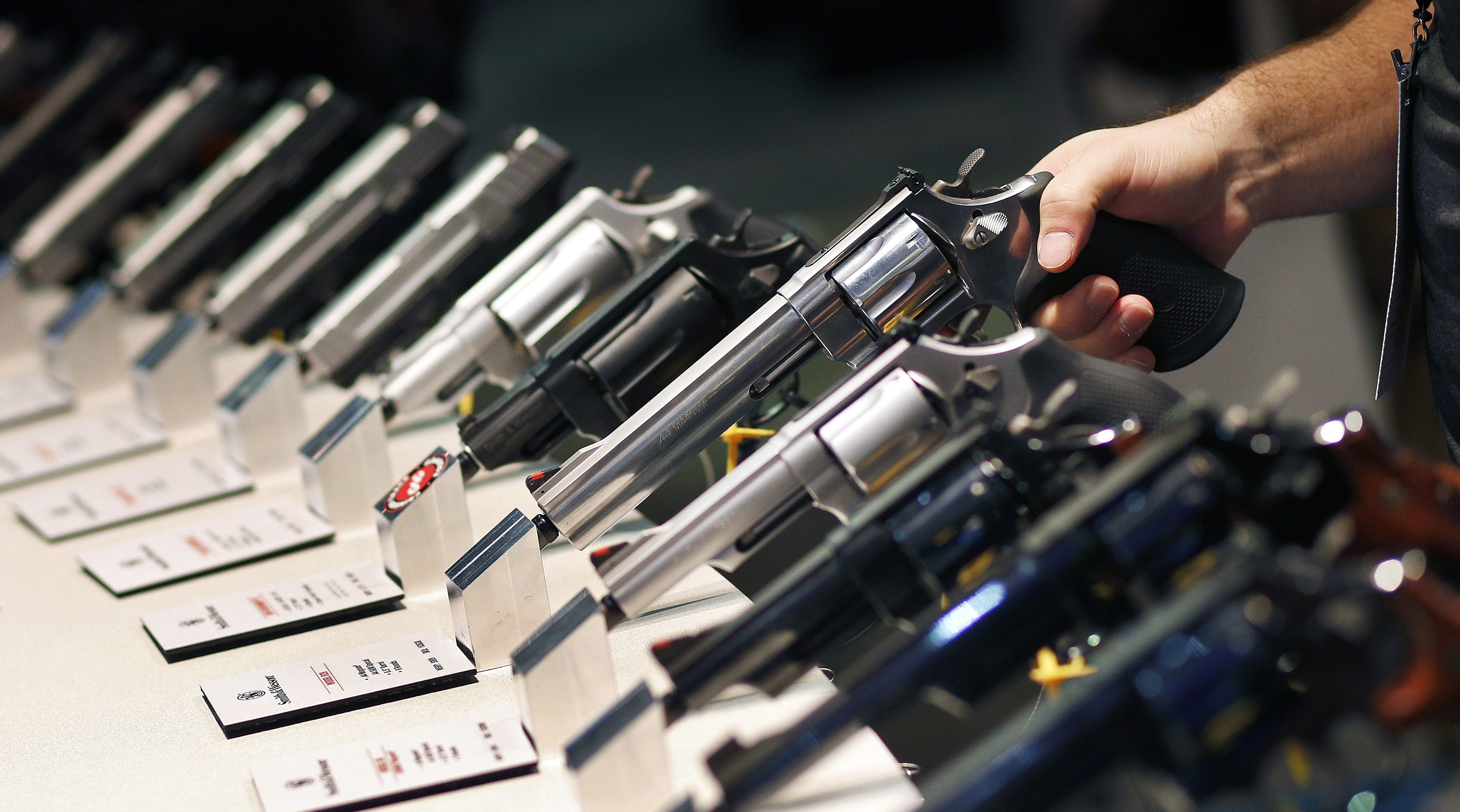 In this Jan. 19, 2016 file photo, handguns are displayed at the Smith & Wesson booth at the Shooting, Hunting and Outdoor Trade Show in Las Vegas. Nearly two-thirds of Americans expressed support for stricter gun laws, according to an Associated Press-GfK poll released Saturday, July 23, 2016. A majority of poll respondents oppose banning handguns.