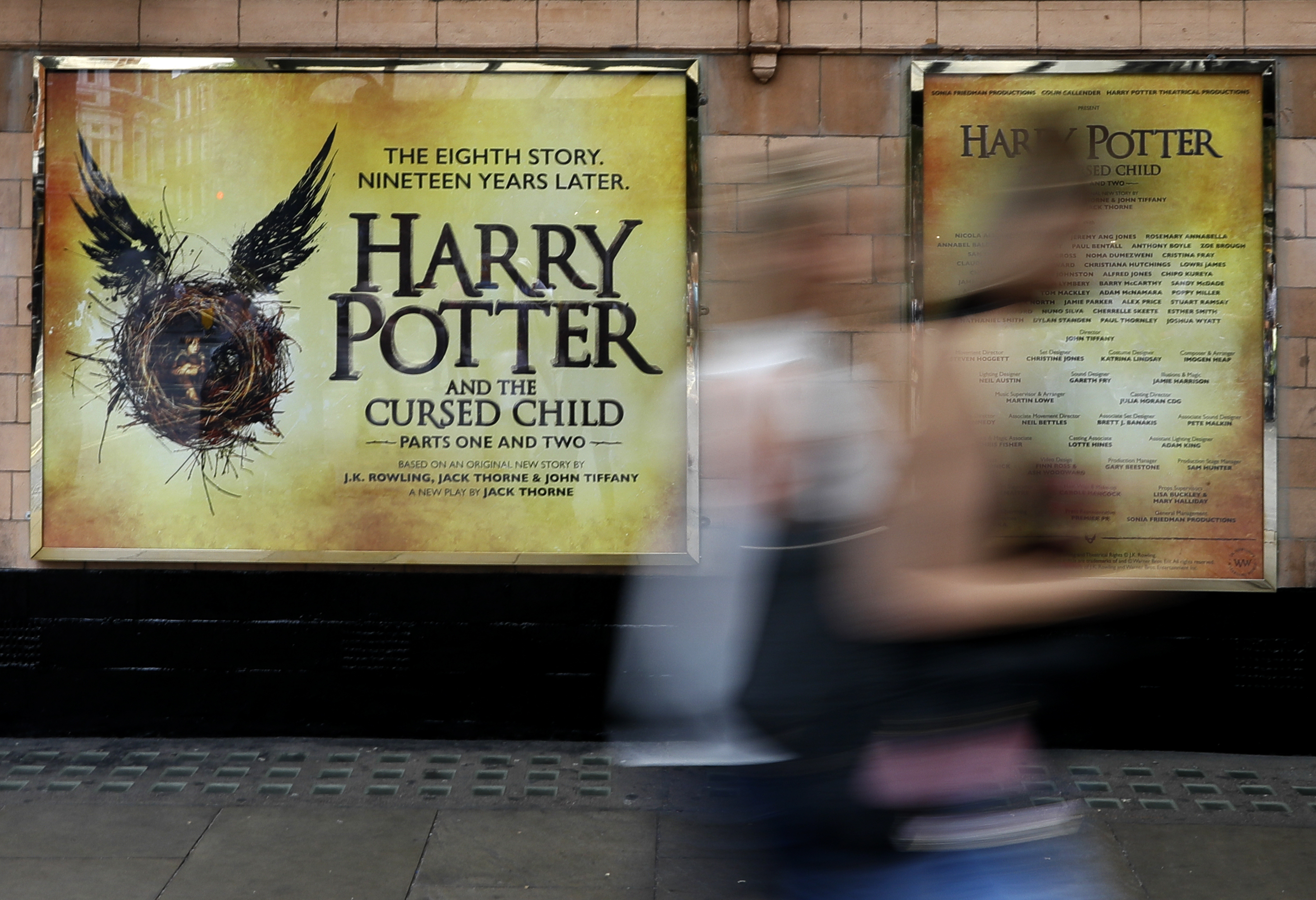 "In this photo taken on Thursday, July 28, 2016, pedestrians pass a poster advertising the new Harry Potter play, at the Palace Theatre in London. Nine years after J.K. Rowling's final novel about the boy wizard, Harry has returned, on the stage and the page - and he's still producing commercial alchemy. ""Harry Potter and the Cursed Child,"" a two-part stage drama that picks up 19 years after the novels ended, has its gala opening Saturday at London's Palace Theatre, and is all-but sold out through December 2017. (AP Photo/Kirsty Wigglesworth)"
