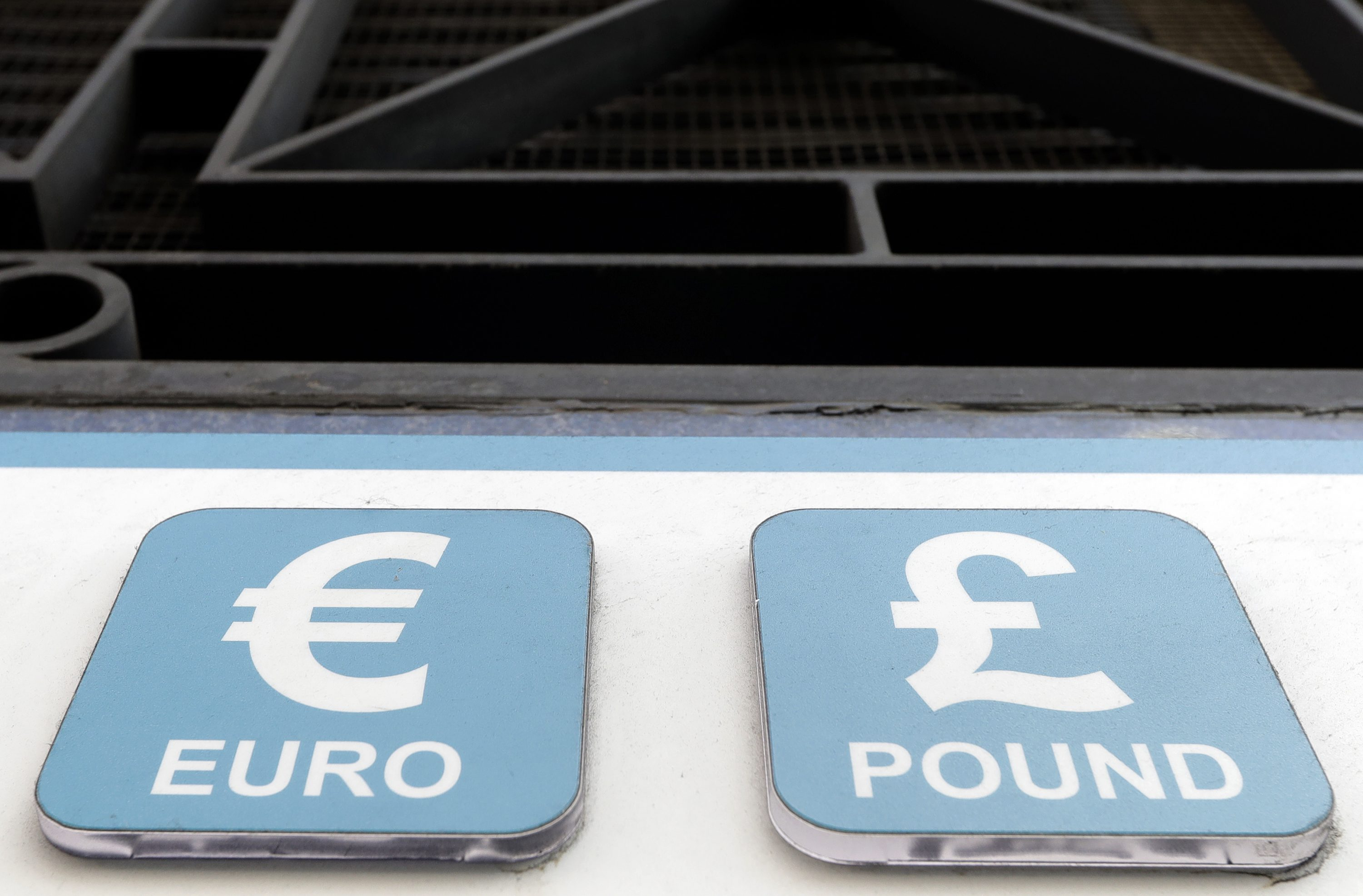 Pound and Euro signs are seen above a cashpoint in London, Tuesday, Oct. 4, 2016. The British pound has hit a 31-year low against the dollar amid concern the country is willing to break away definitively from the European Union's common market.