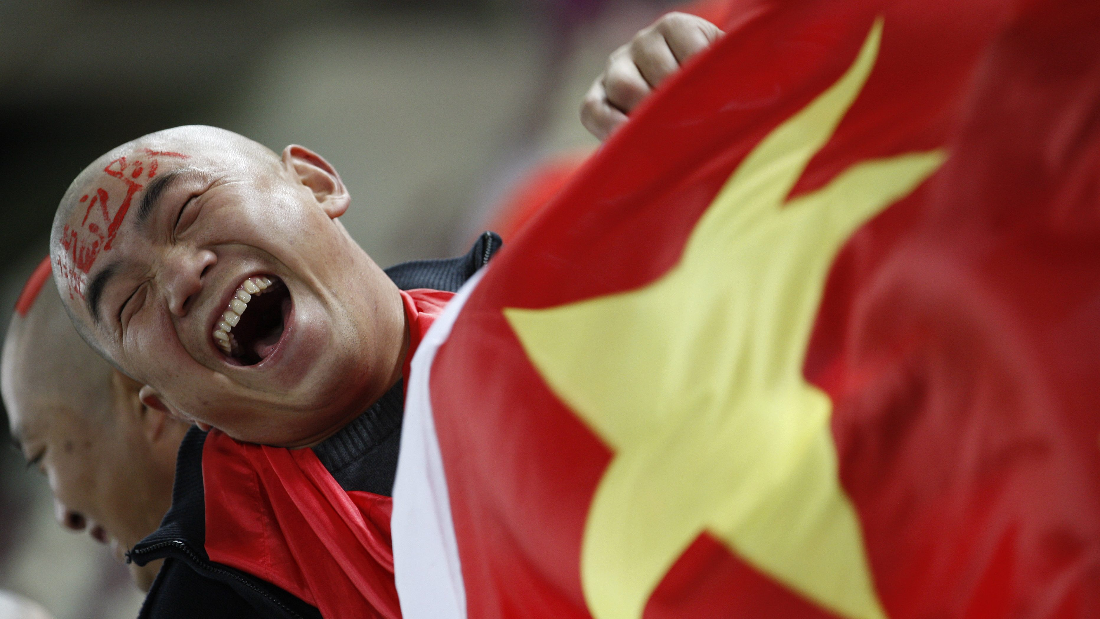 FILE - In this Wednesday, Jan. 12, 2011, file photo, a Chinese soccer fan cheers for his team before their AFC Asian Cup group A soccer match against Qatar in Doha, Qatar. Ever since the Chinese Football Association announced it had coaxed Lippi out of retirement, the nation's long-suffering fans have responded with more than a hint of skepticism. Given the team's record of failure under a string of foreign and Chinese coaches, the problems are more often attributed to the lack of a strong youth program and a misplaced, money-driven focus on the domestic league.