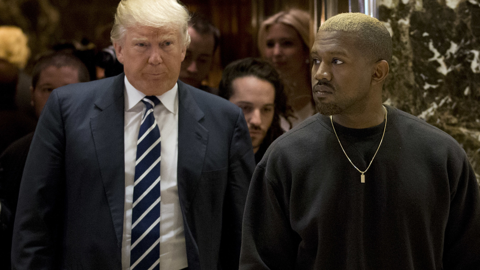 Kanye West and President-elect Donald Trump arrive to the lobby of Trump Tower in New York, Tuesday, Dec. 13, 2016. (AP Photo/Seth Wenig)