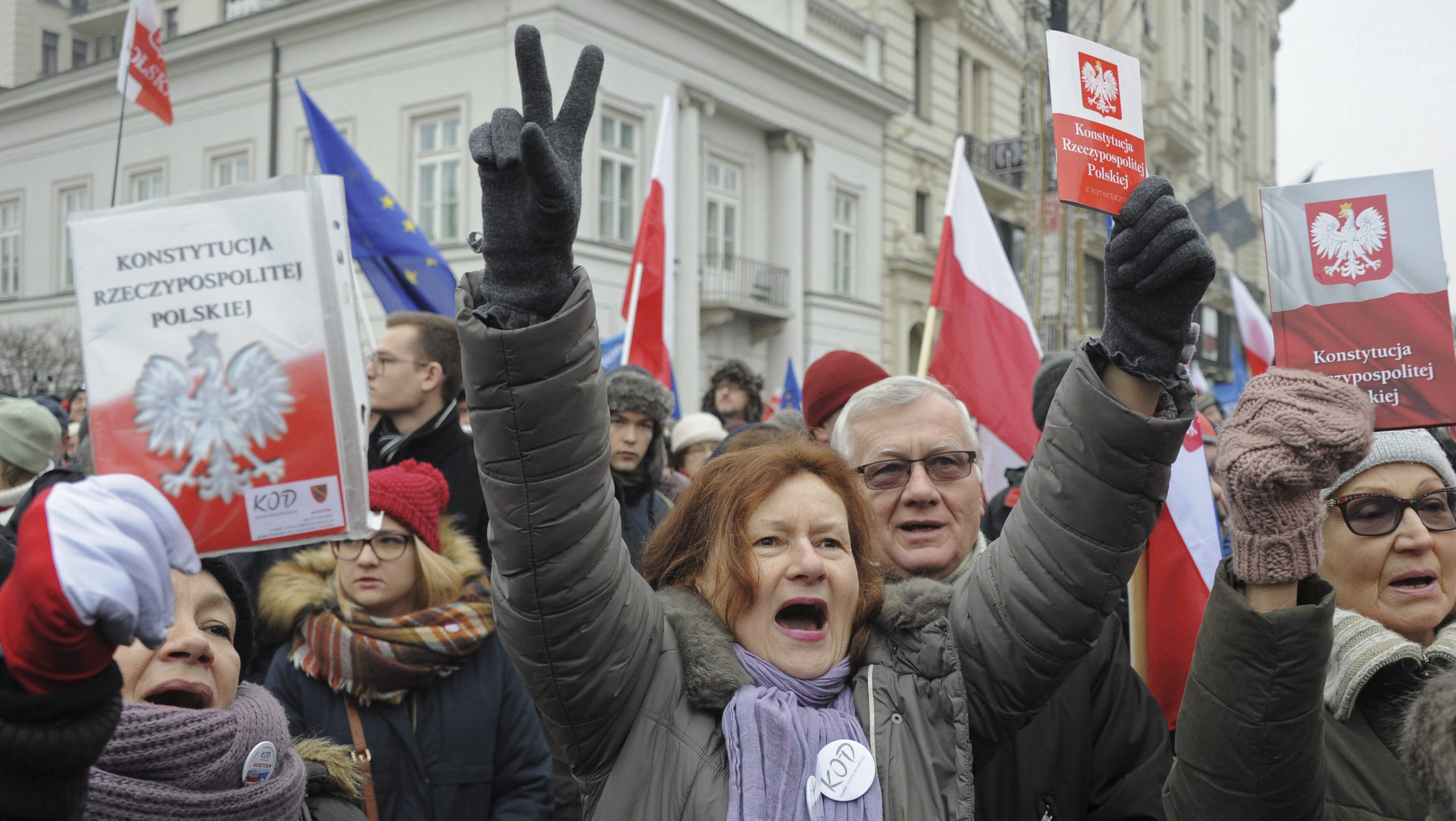 Protesters holding copies of Poland's constitution shout slogans during an anti-government demonstration, in Warsaw, Poland, Saturday, Dec. 17, 2016. Opponents of the country's populist government are staging a new protest outside the presidential palace in an appeal to the head of state to protect the young democracy's constitutional order from a series of government steps they deem anti-democratic. (AP Photo/Alik Keplicz)